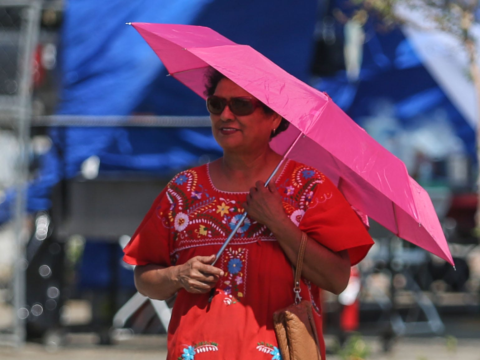 A woman with an umbrella at the Mexican independence day celebration at Our Virgin of Guadalupe Church in Mecca on Saturday, September 15, 2018.