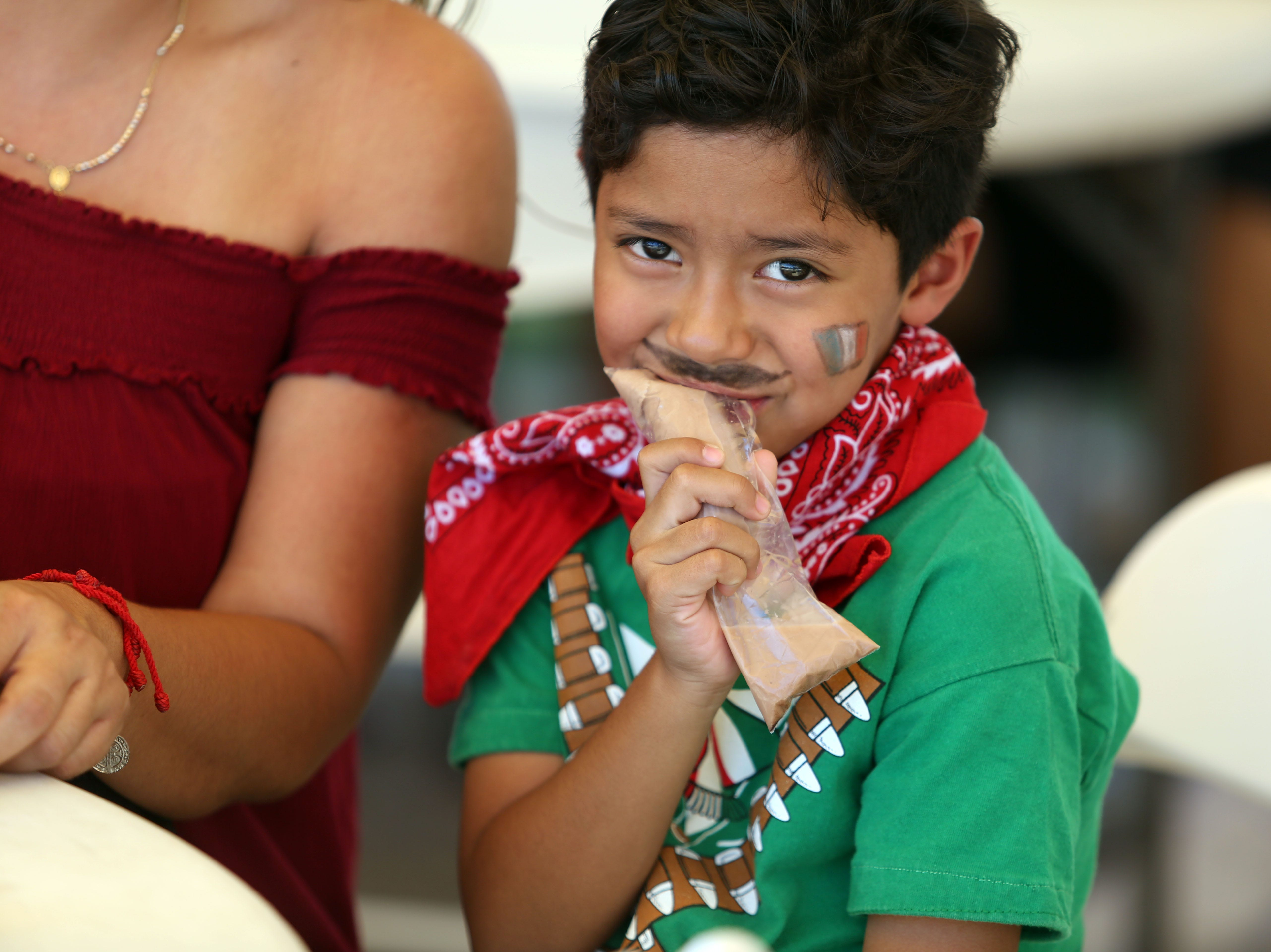 Sergio Bautista, 6, has a snack at the Mexican independence day celebration at Our Virgin of Guadalupe Church in Mecca on Saturday, September 15, 2018.