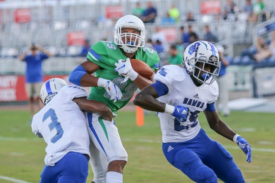 UWF's Quentin Randolph (29), a Navarre High School graduate, makes a catch as Shorter defenders try to knock the ball out of his hands at Blue Wahoos Stadium on Saturday, September 15, 2018.