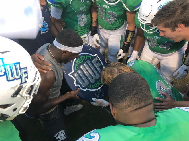 """UWF linebacker Austin Dukes (34) puts the first signature  on the """"Turnover Shield"""" in the  Argos' win over Shorter on Sept. 15, 2018."""