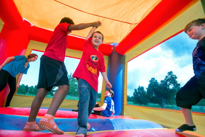 Dominic Barone, 8, center, plays with friends Sunday during a surprise party at a Cantonment park to celebrate his victory over leukemia.