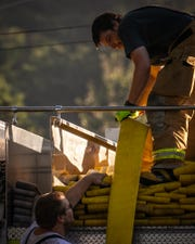 Firefighters pack up some of the 4,500 feet of supply hoseline used after a early morning house fire that left eight people homeless and killed a service dog in the 600 block of Irishtown Rd., Sunday, Sept. 16, 2018, in Oxford Township. The cause of the fire was accidental, said assistant chief Bryan Long of the Irishtown Fire Company.