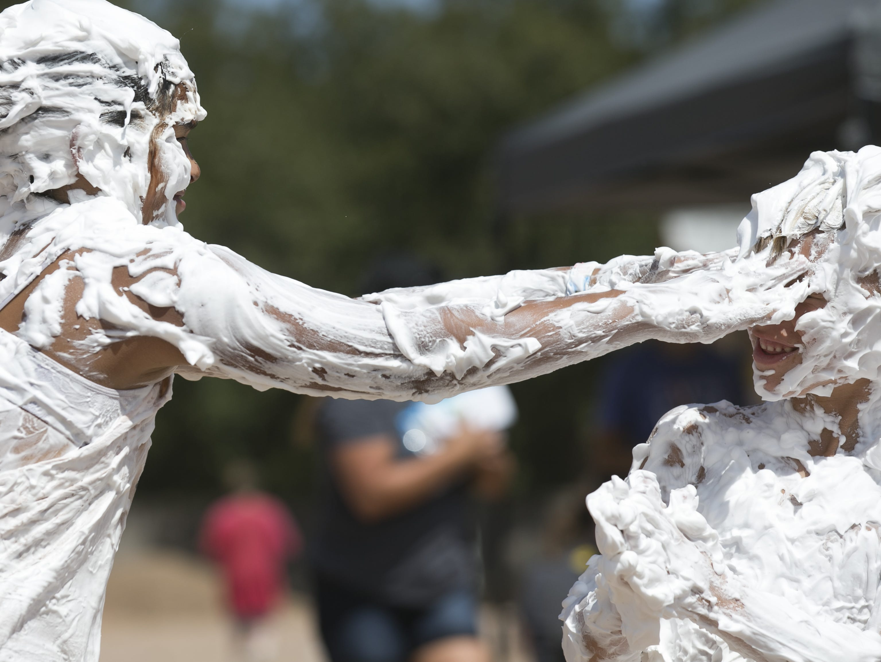 10-year-old Thalia Loya (left) rubs shaving cream in 6-year-old Easton Tamuty's face (right) at the third annual Messy Fest in Queen Creek on Saturday, Sept. 15, 2018.