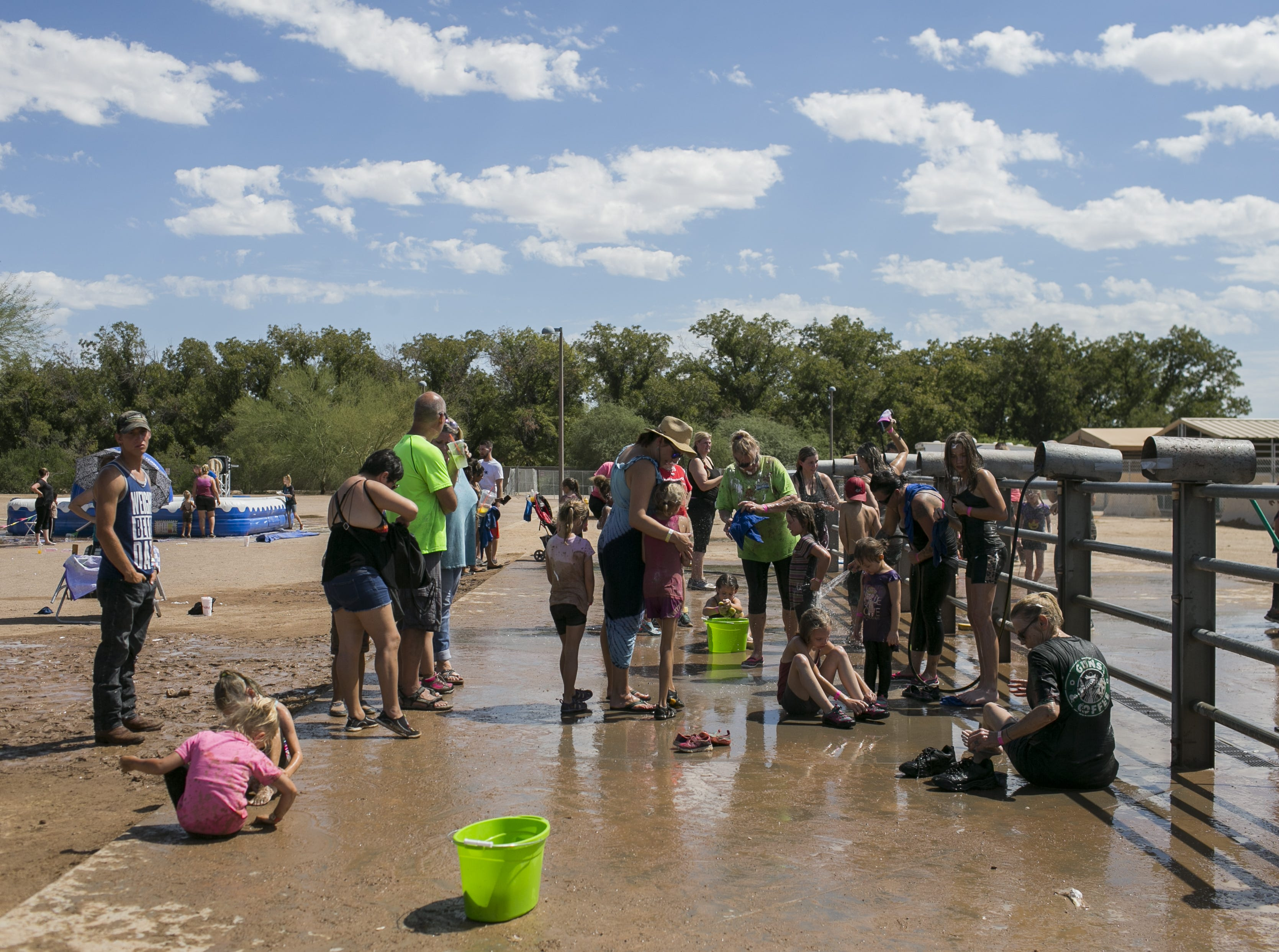 Families line up to rinse off at the the third annual Messy Fest in Queen Creek on Saturday, Sept. 15, 2018.