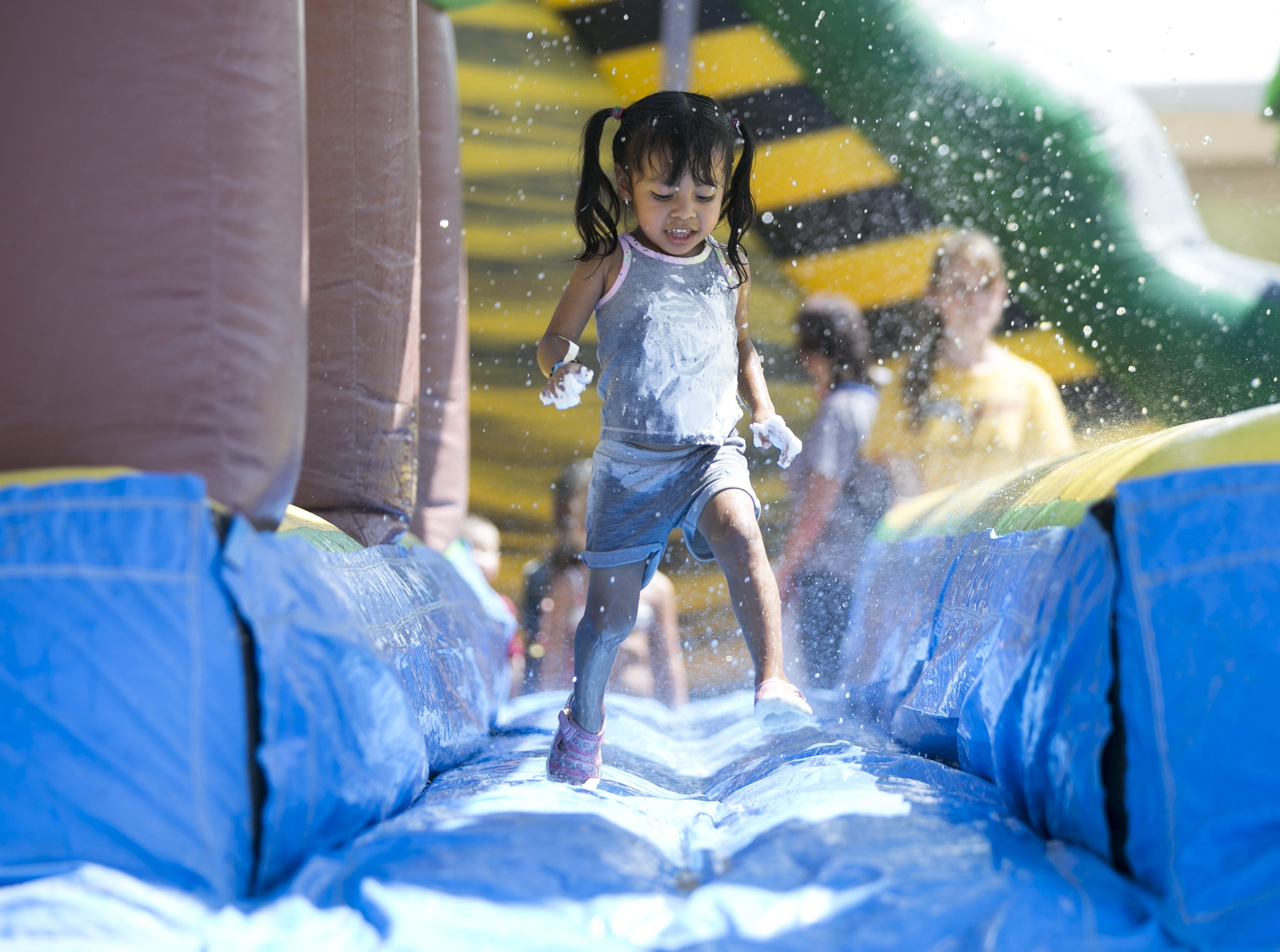 3-year-old Camilla Silva runs through a wet bounce house at the third annual Messy Fest in Queen Creek on Saturday, Sept. 15, 2018.