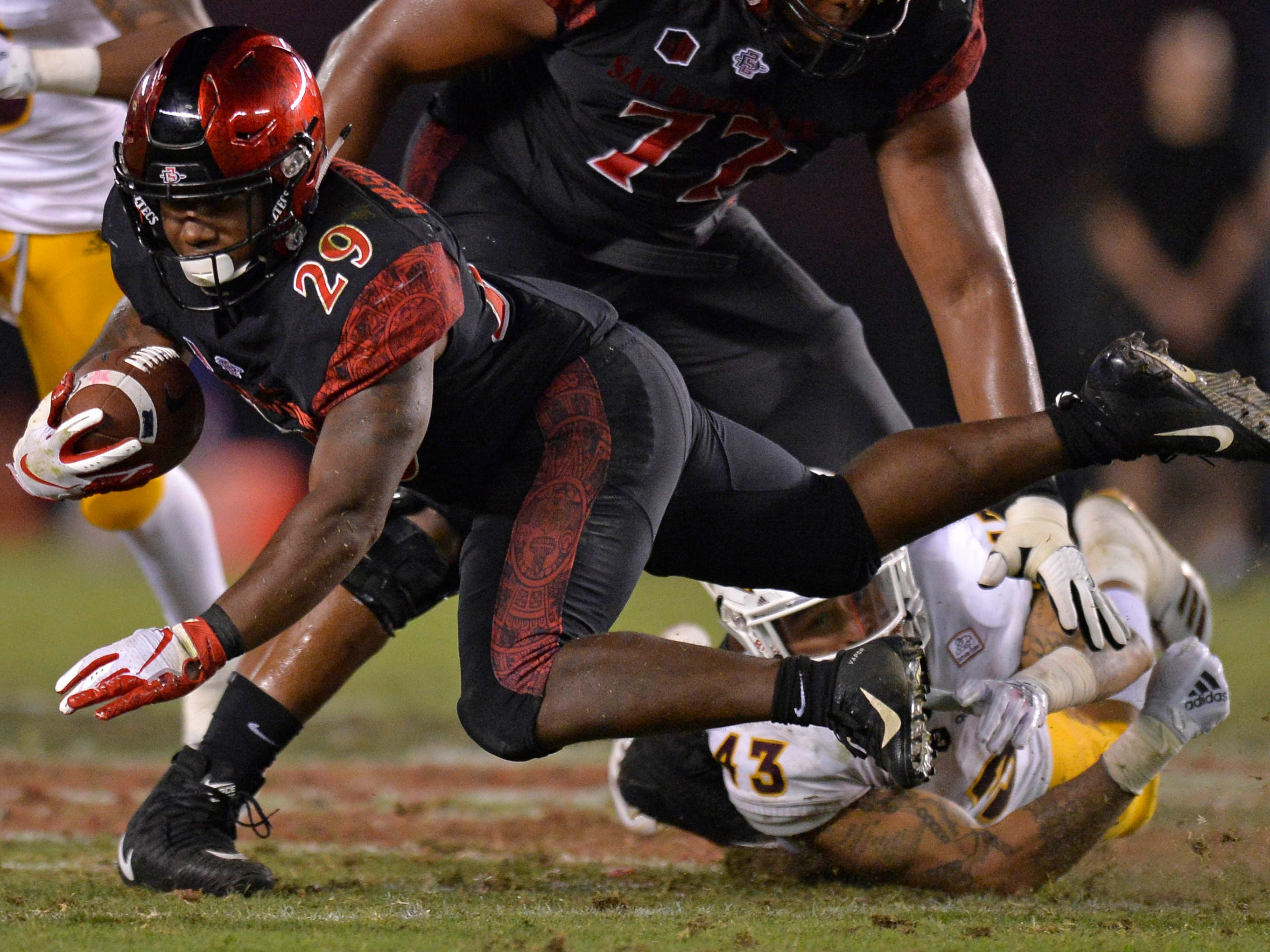 Sep 15, 2018; San Diego, CA, USA; San Diego State Aztecs running back Juwan Washington (29) is tripped up by Arizona State Sun Devils safety Jalen Harvey (43) during the third quarter at SDCCU Stadium. Mandatory Credit: Jake Roth-USA TODAY Sports