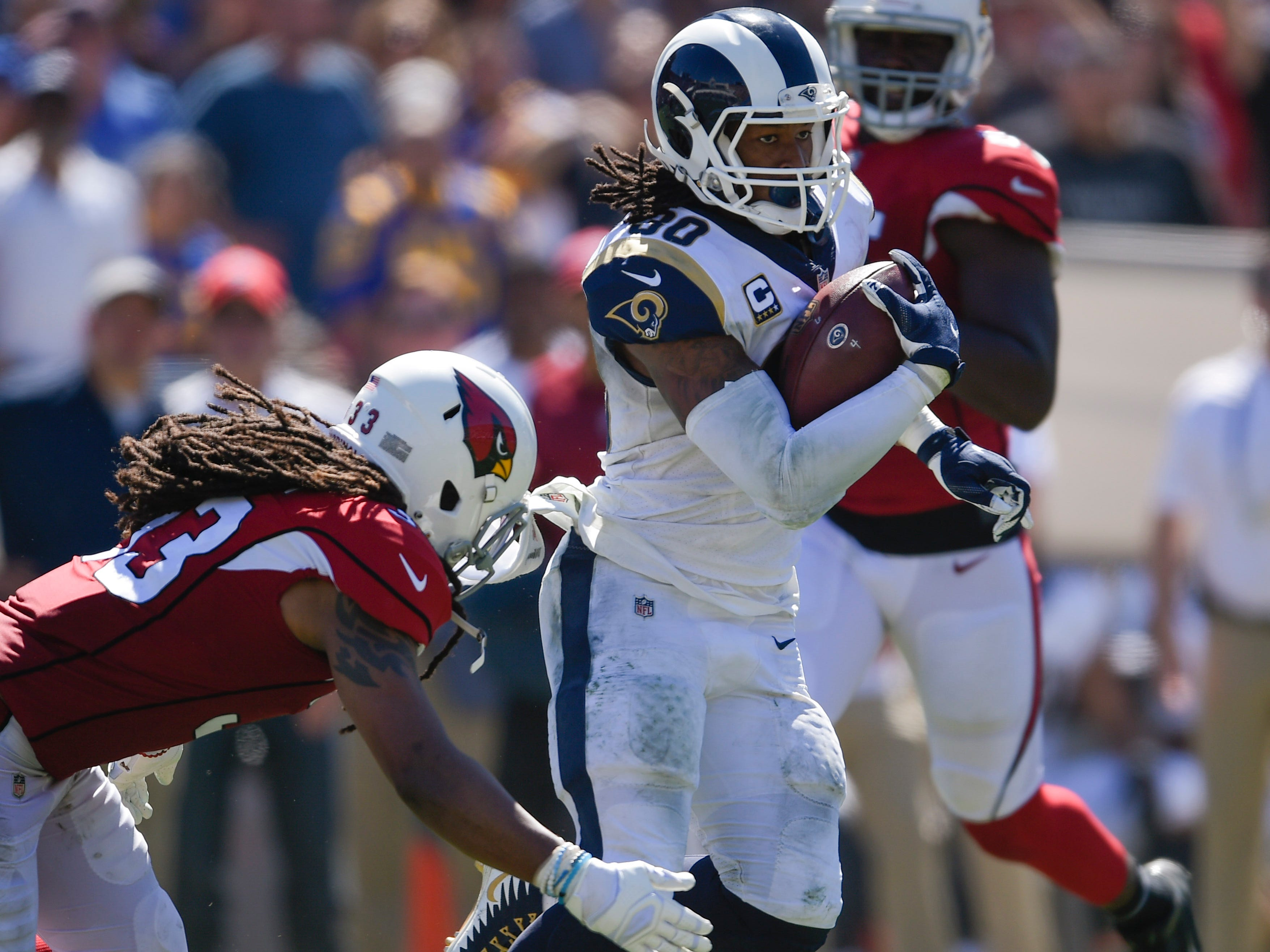 Sep 16, 2018; Los Angeles, CA, USA; Los Angeles Rams running back Todd Gurley II (30) runs the ball past Arizona Cardinals safety Tre Boston (33) during the first half at Los Angeles Memorial Coliseum. Mandatory Credit: Kelvin Kuo-USA TODAY Sports