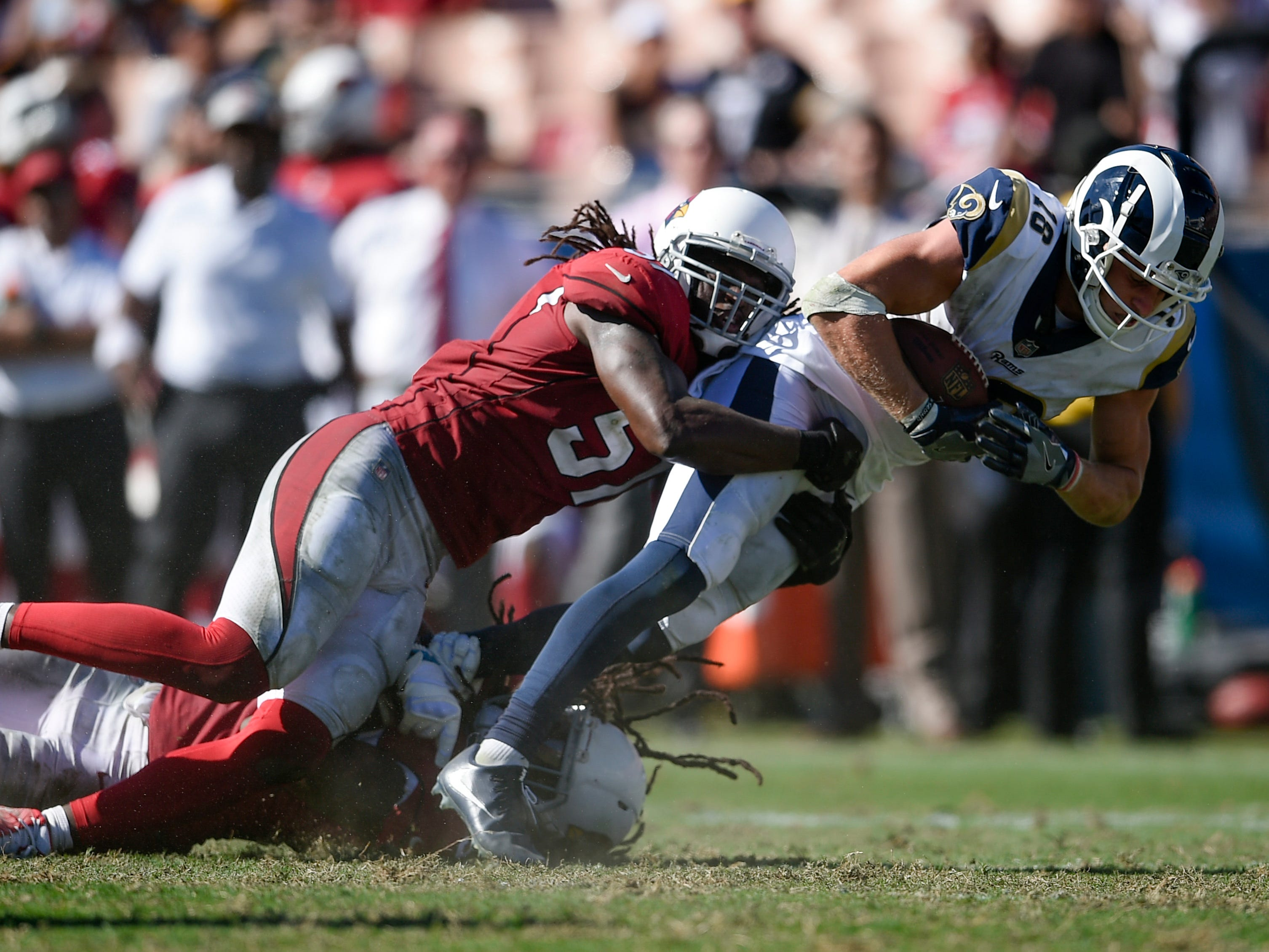 Sep 16, 2018; Los Angeles, CA, USA; Los Angeles Rams wide receiver Cooper Kupp (18) falls for extra yards while being tackled by Arizona Cardinals linebacker Josh Bynes (57) during the second half at Los Angeles Memorial Coliseum. Mandatory Credit: Kelvin Kuo-USA TODAY Sports