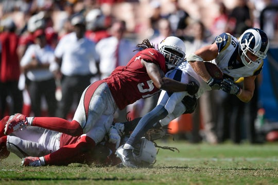 Rams receiver Cooper Kupp is dragged down by Cardinals linebacker Josh Bynes during the second half of a game at Los Angeles Memorial Coliseum.