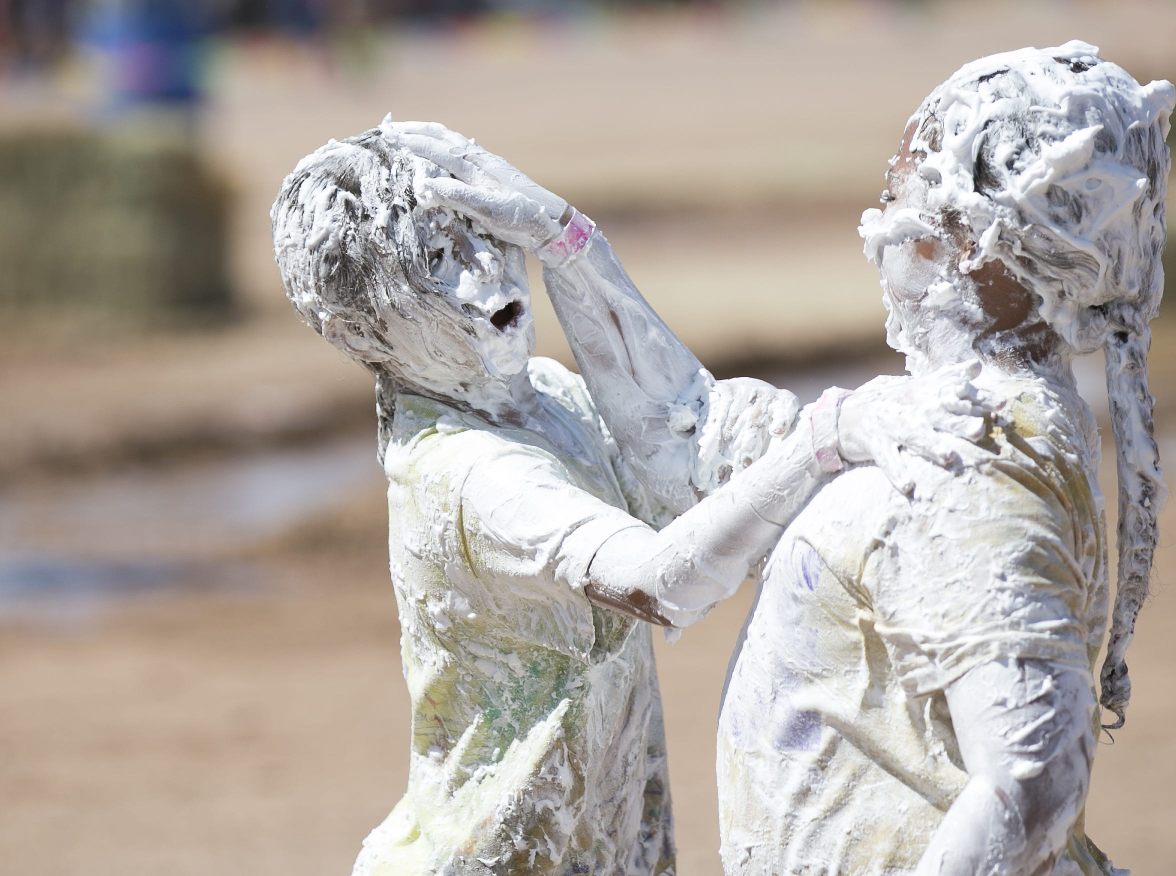 8-year-old Olivia Dlott (left) and 8-year-old Mia Hall (right) rub shaving cream on each other's faces at the third annual Messy Fest in Queen Creek on Saturday, Sept. 15, 2018.