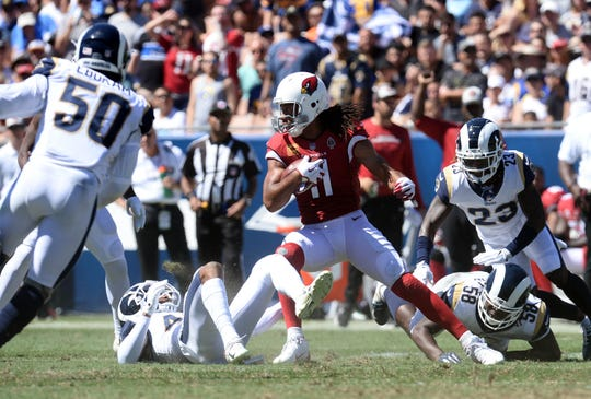 Cardinals receiver Larry Fitzgerald runs with the ball during the first half of a game against he Rams.