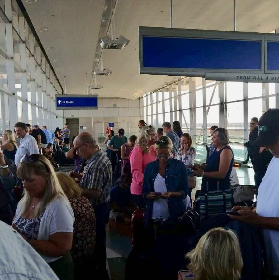 Passengers wait while police investigate an unattended vehicle at Terminal 4 at Sky Harbor Airport on Sept. 16, 2018.