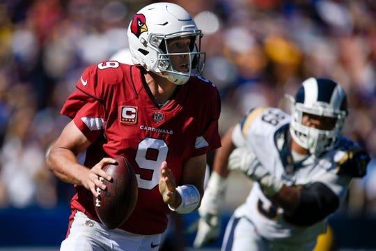 Cardinals quarterback Sam Bradford look to throw the ball while under pressure from the Rams during a game at Los Angeles Memorial Coliseum.