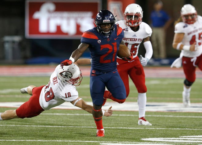 Arizona running back J.J. Taylor (21) breaks the tackle from Southern Utah place kicker Manny Berz (18) and scores a touchdown on a kickoff in the first half during an NCAA college football game, Saturday, Sept. 15, 2018, in Tucson, Ariz. (AP Photo/Rick Scuteri)