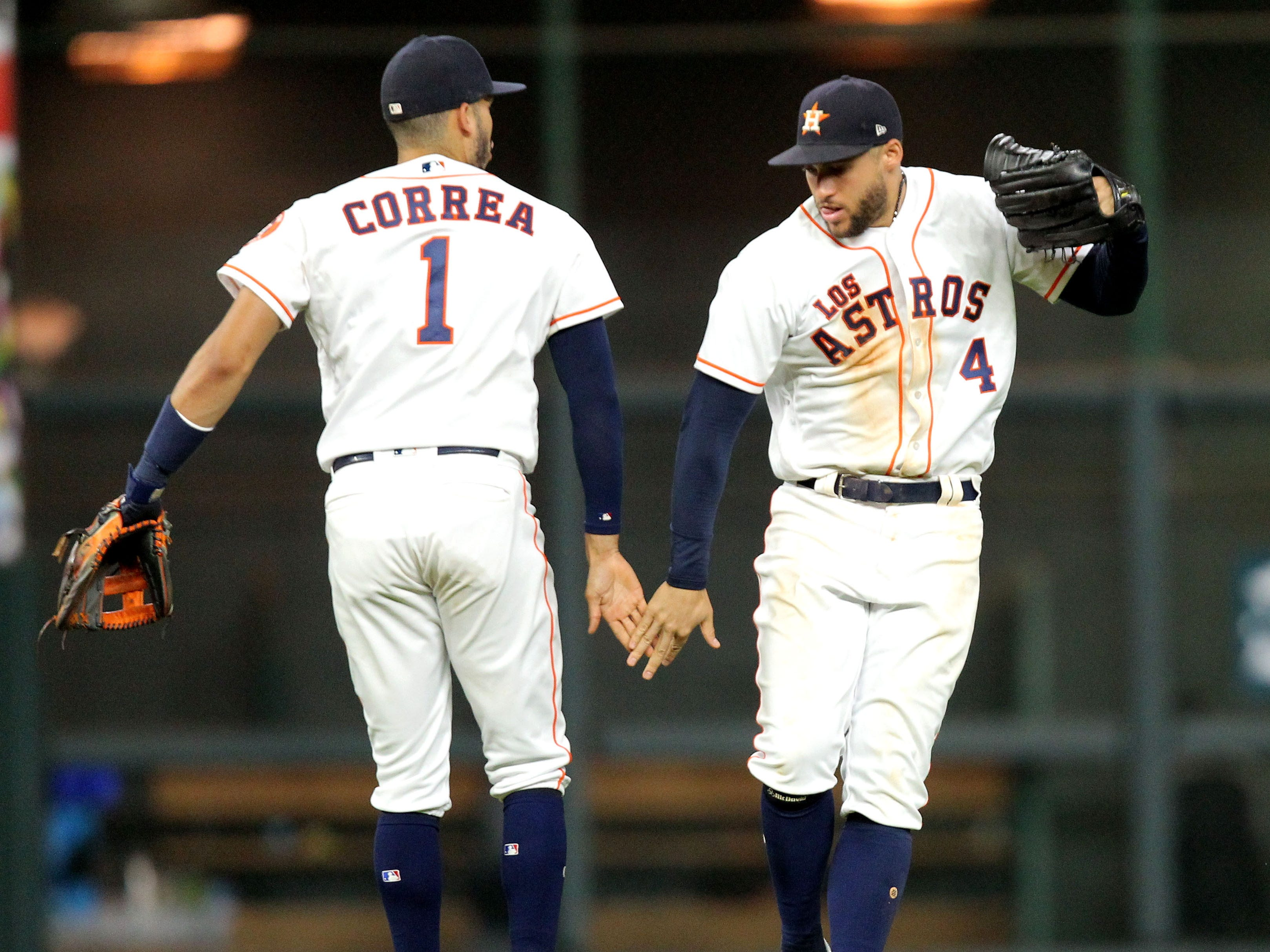 Sep 15, 2018; Houston, TX, USA; Houston Astros shortstop Carlos Correa (1, left) and center fielder George Springer (4, right) celebrate after the final out of Houston's 10-4 win over the Arizona Diamondbacks at Minute Maid Park. Mandatory Credit: Erik Williams-USA TODAY Sports