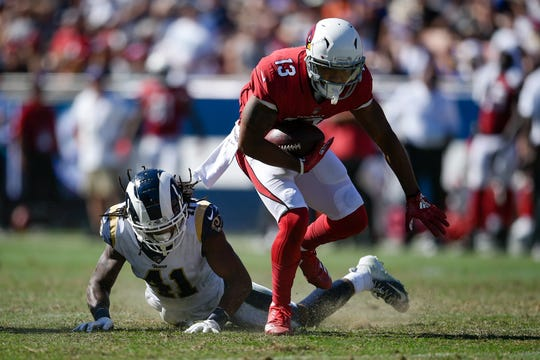 Rams safety Marqui Christian tries to bring down Cardinals receiver Christian Kirk.