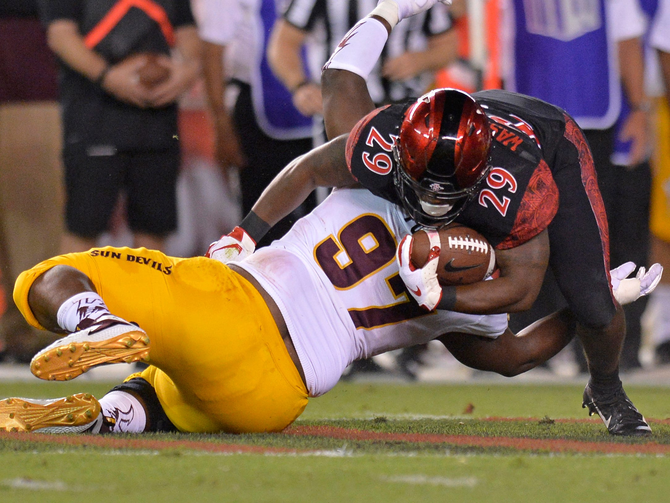 Sep 15, 2018; San Diego, CA, USA; San Diego State Aztecs running back Juwan Washington (29) is tackled by Arizona State Sun Devils defensive lineman Shannon Forman (97) during the first quarter at SDCCU Stadium. Mandatory Credit: Jake Roth-USA TODAY Sports