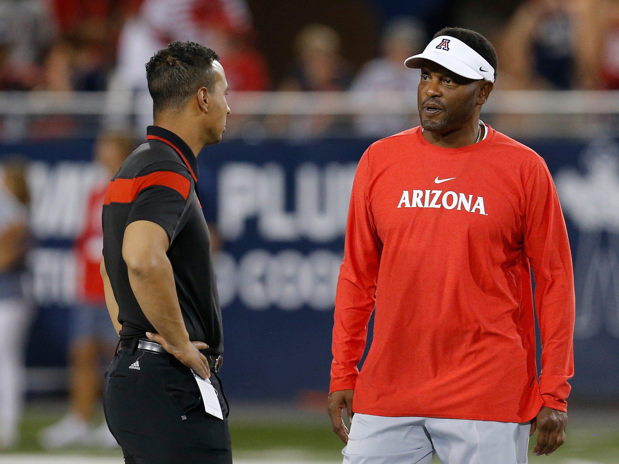 Southern Utah head coach Demario Warren and Arizona head coach Kevin Sumlin talk before an NCAA college football game, Saturday, Sept. 15, 2018, in Tucson, Ariz. (AP Photo/Rick Scuteri)