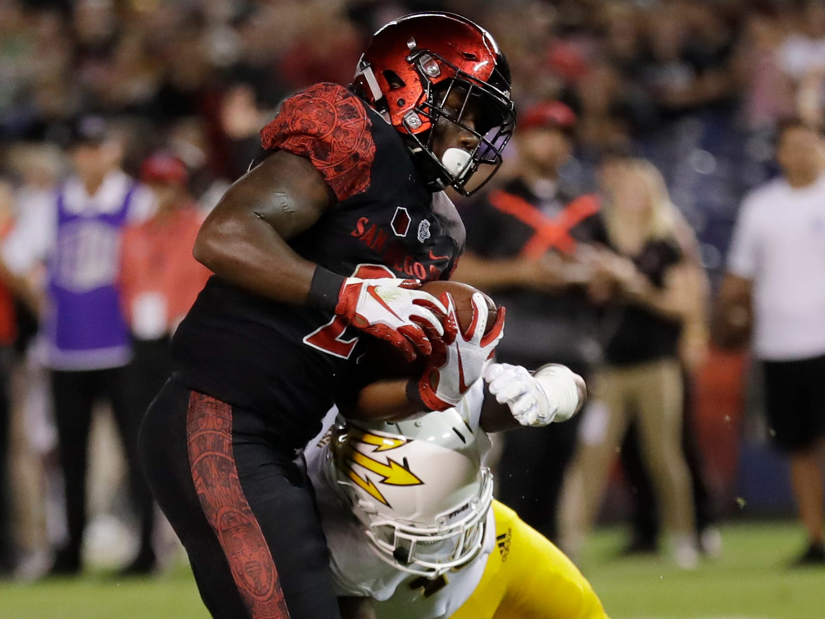San Diego State running back Juwan Washington, left, gets past Arizona State safety Aashari Crosswell as he scores a touchdown during the first half of an NCAA college football game Saturday, Sept. 15, 2018, in San Diego. (AP Photo/Gregory Bull)