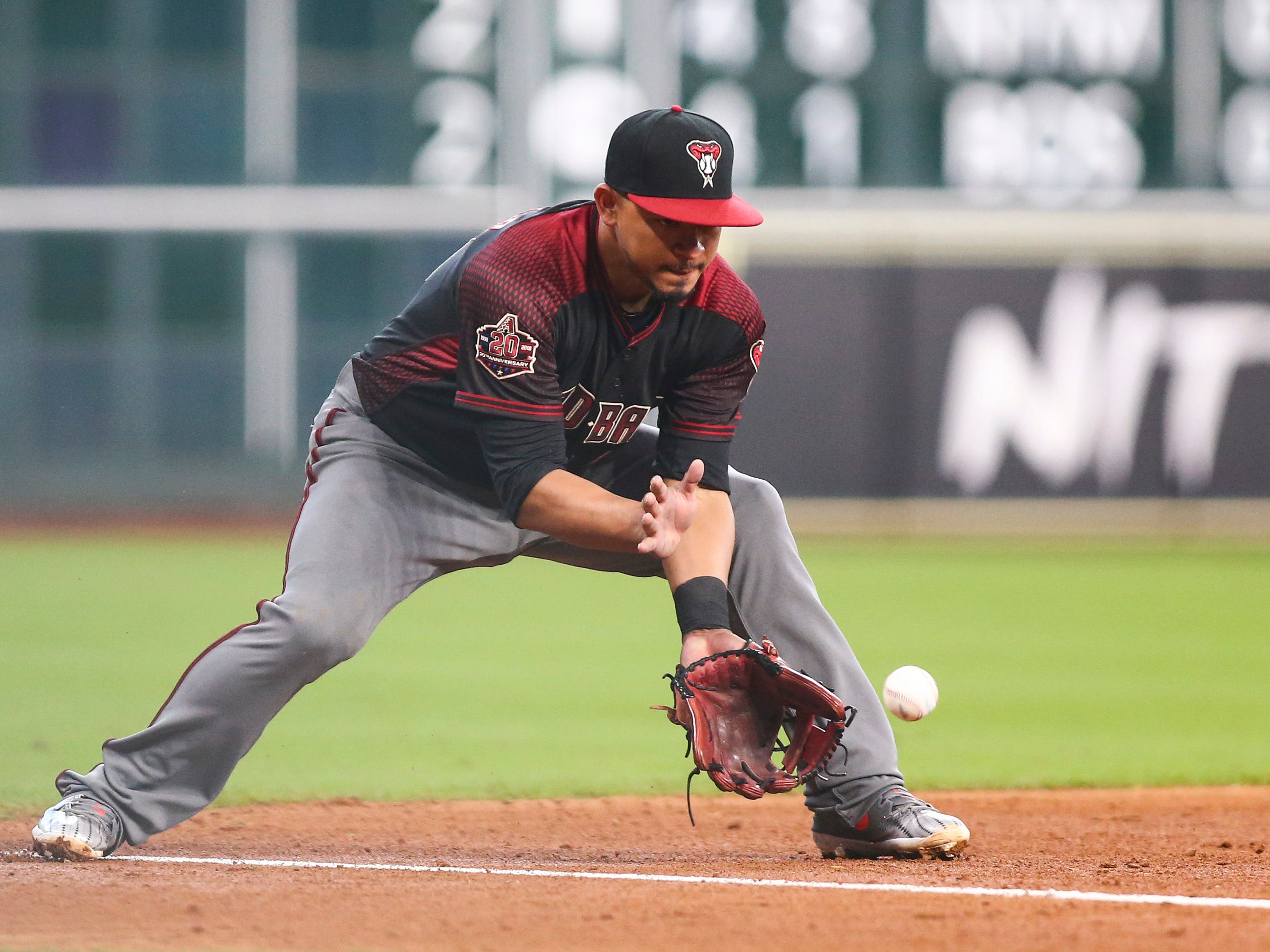 Sep 16, 2018; Houston, TX, USA; Arizona Diamondbacks third baseman Eduardo Escobar (14) fields a ground ball during the fourth inning against the Houston Astros at Minute Maid Park. Mandatory Credit: Troy Taormina-USA TODAY Sports