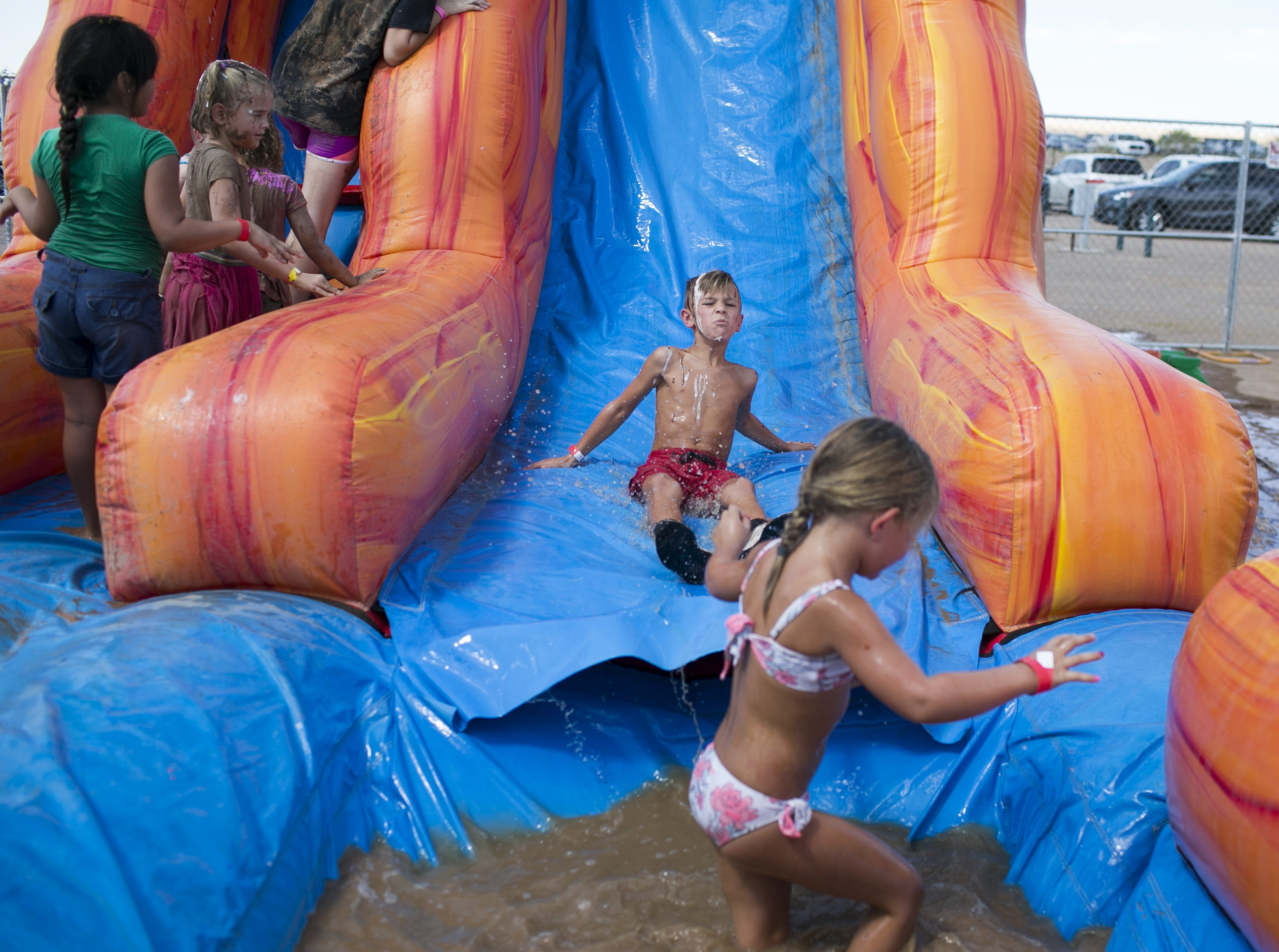 6-year-old Easton Tamuty slides into a pool of muddy water at the third annual Messy Fest in Queen Creek on Saturday, Sept. 15, 2018.