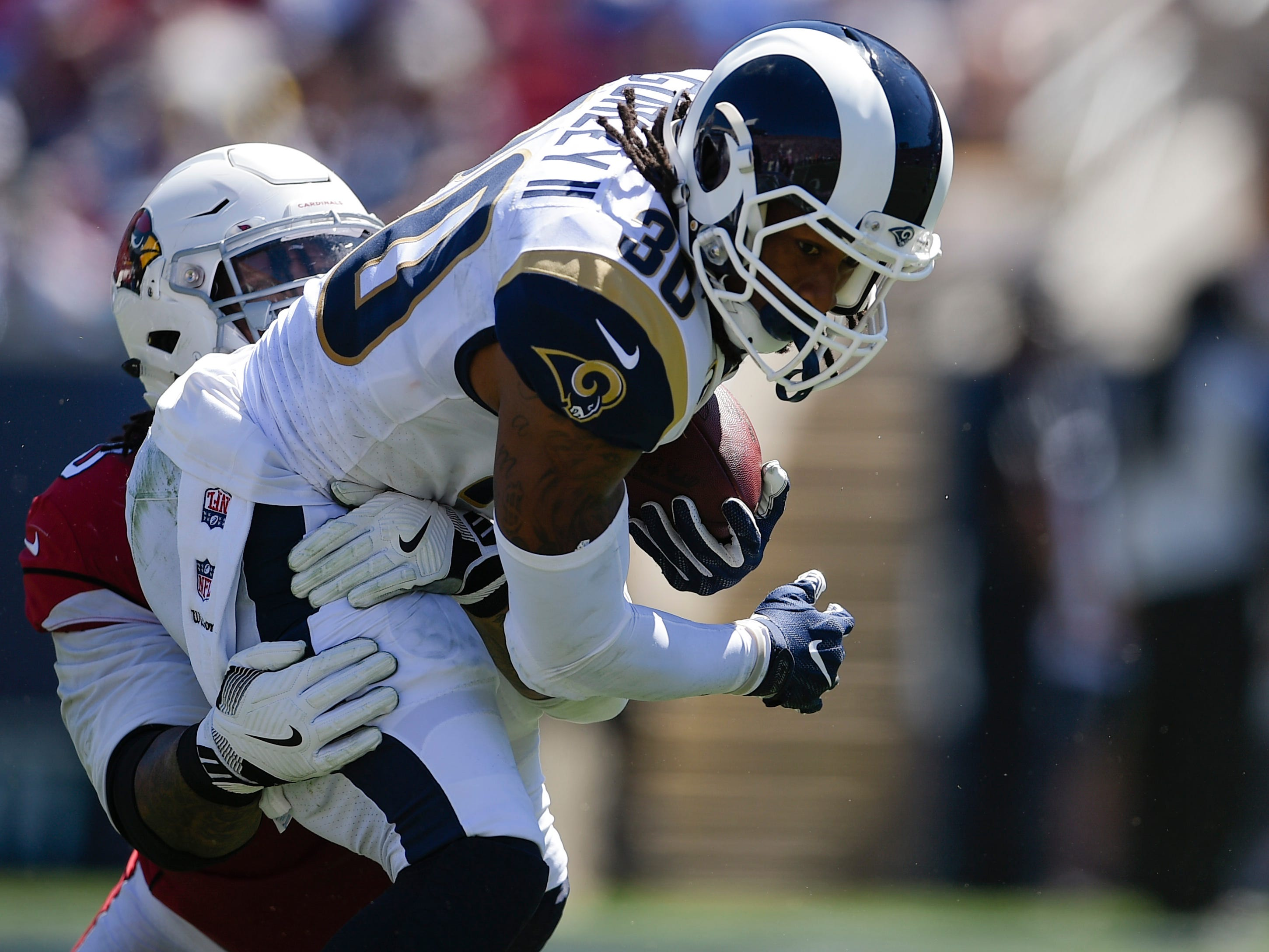 Sep 16, 2018; Los Angeles, CA, USA; Los Angeles Rams running back Todd Gurley II (30) runs the ball while being tackled by Arizona Cardinals defensive tackle Robert Nkemdiche (90) during the first half at Los Angeles Memorial Coliseum. Mandatory Credit: Kelvin Kuo-USA TODAY Sports