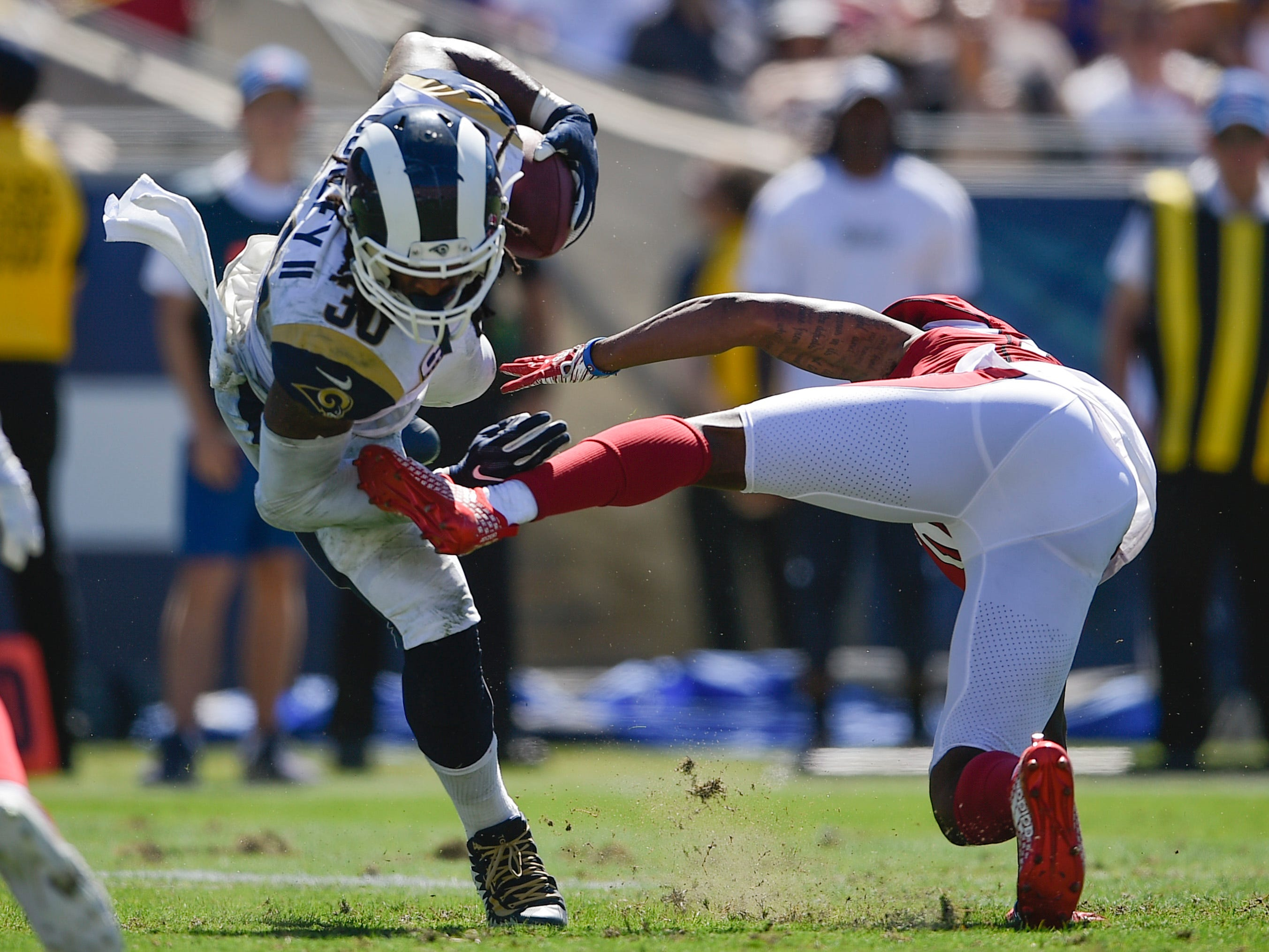 Sep 16, 2018; Los Angeles, CA, USA; Arizona Cardinals cornerback Bene Benwikere (23) tackles Los Angeles Rams running back Todd Gurley II (30) during the first half at Los Angeles Memorial Coliseum. Mandatory Credit: Kelvin Kuo-USA TODAY Sports
