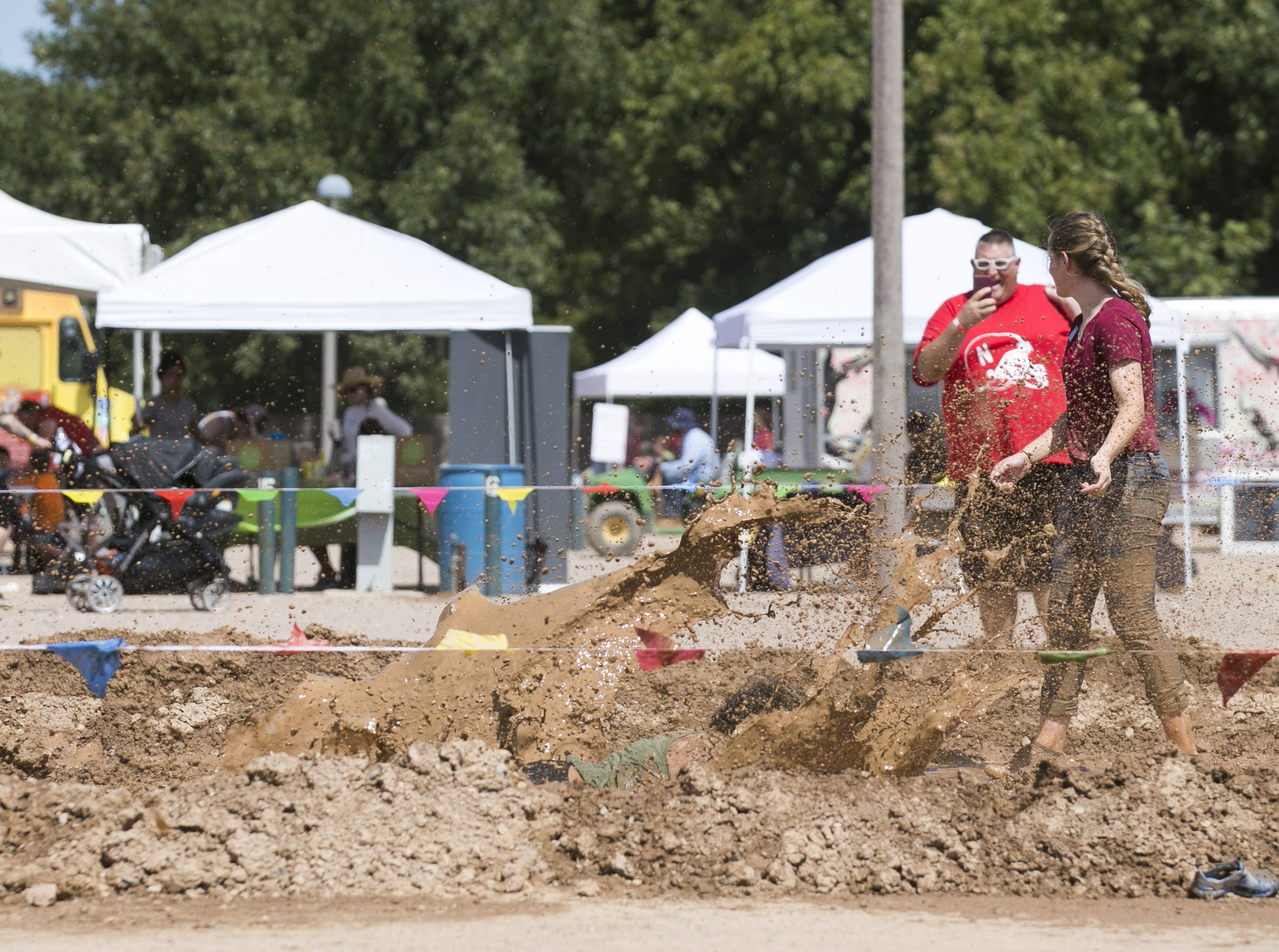 17-year-old Raven McCoo takes a dive into a mud pit at the third annual Messy Fest in Queen Creek on Saturday, Sept. 15, 2018.