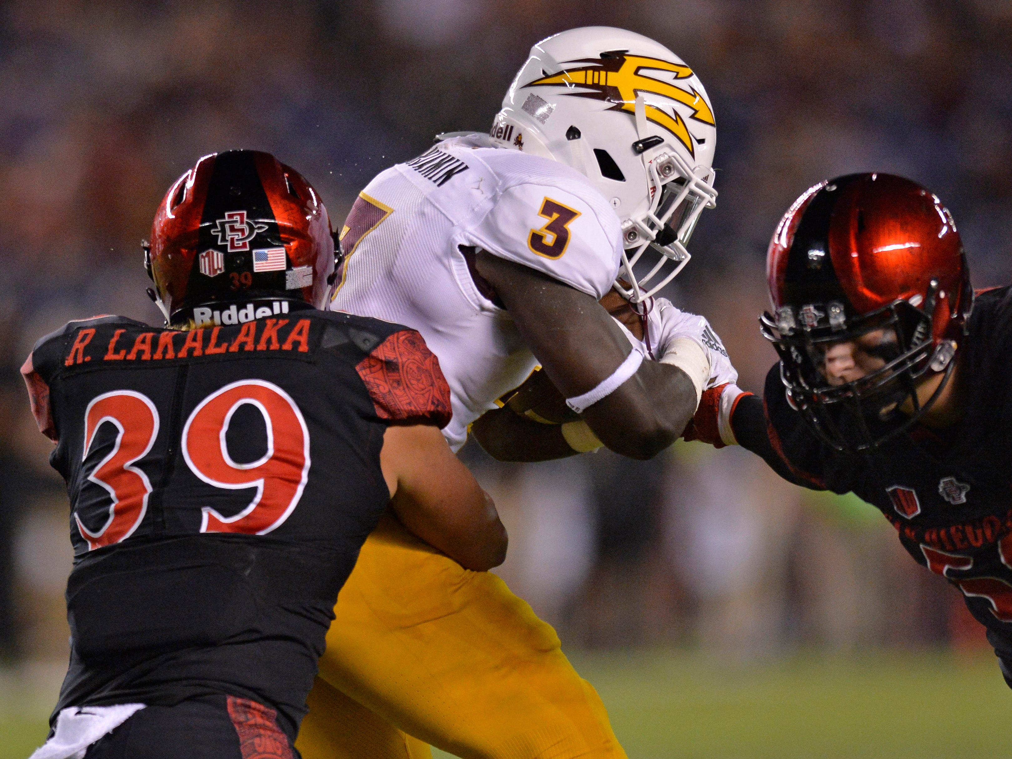 Sep 15, 2018; San Diego, CA, USA; Arizona State Sun Devils running back Eno Benjamin (3) is defended by San Diego State Aztecs linebacker Ronley Lakalaka (39) and defensive lineman Connor Mitchell (58) during the first quarter at SDCCU Stadium. Mandatory Credit: Jake Roth-USA TODAY Sports