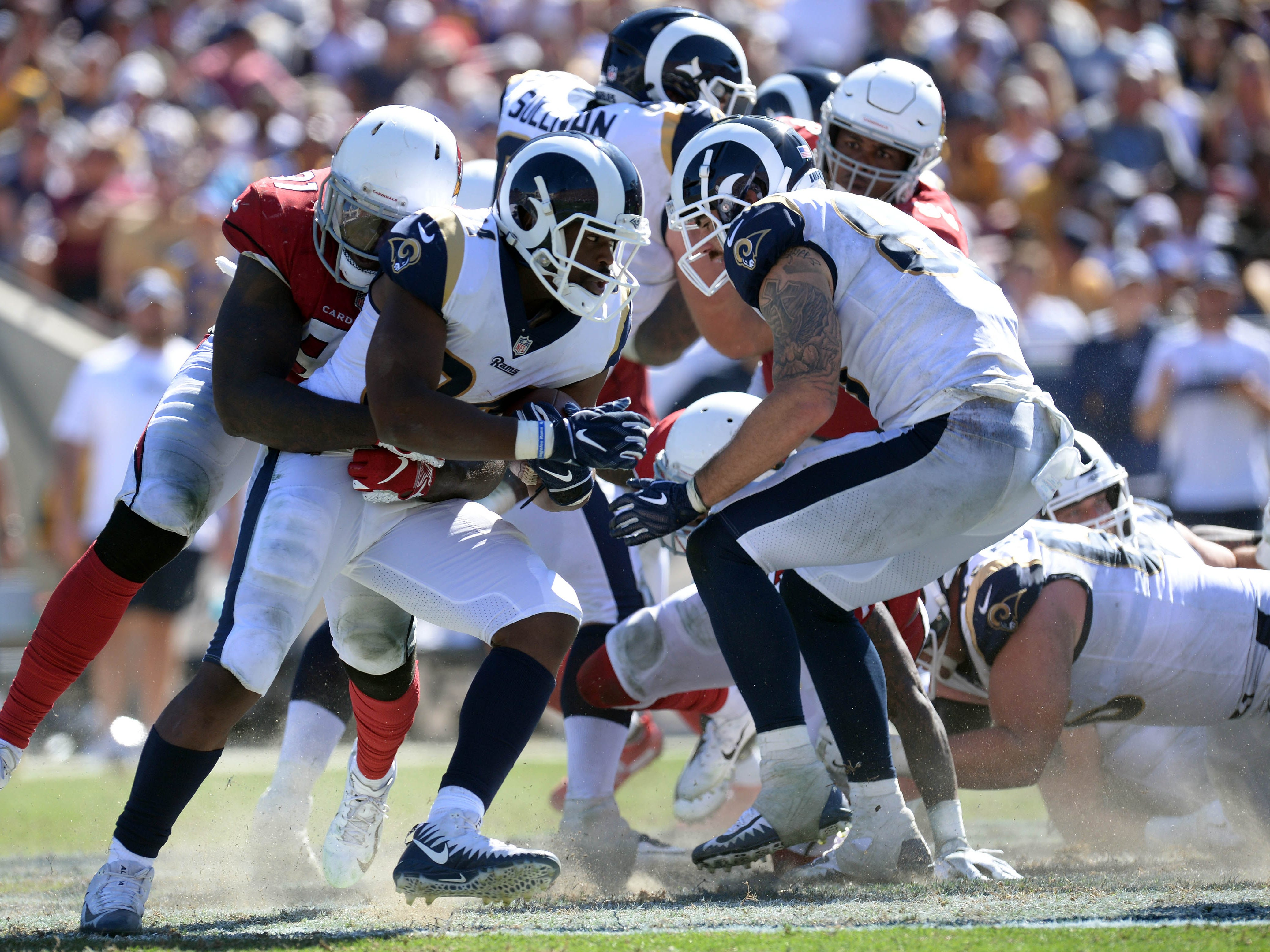 September 16, 2018; Los Angeles, CA, USA; Los Angeles Rams running back Malcolm Brown (34) is brought down by Arizona Cardinals defensive end Benson Mayowa (91) during the second half at the Los Angeles Memorial Coliseum. Mandatory Credit: Gary A. Vasquez-USA TODAY Sports