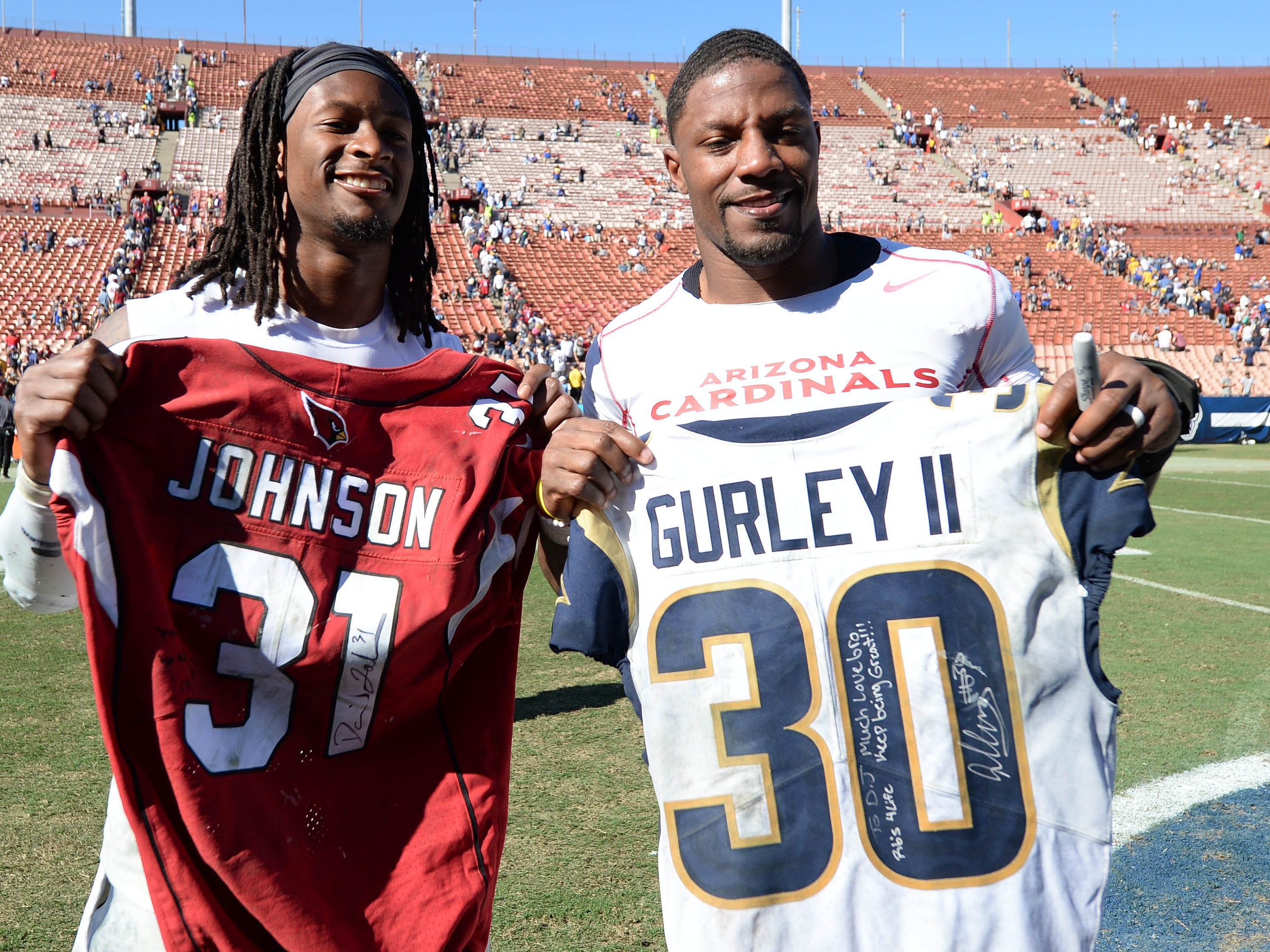 September 16, 2018; Los Angeles, CA, USA; Los Angeles Rams running back Todd Gurley (30) and Arizona Cardinals running back David Johnson (31) pose for a photo after exchanging jerseys following the game at the Los Angeles Memorial Coliseum. Mandatory Credit: Gary A. Vasquez-USA TODAY Sports