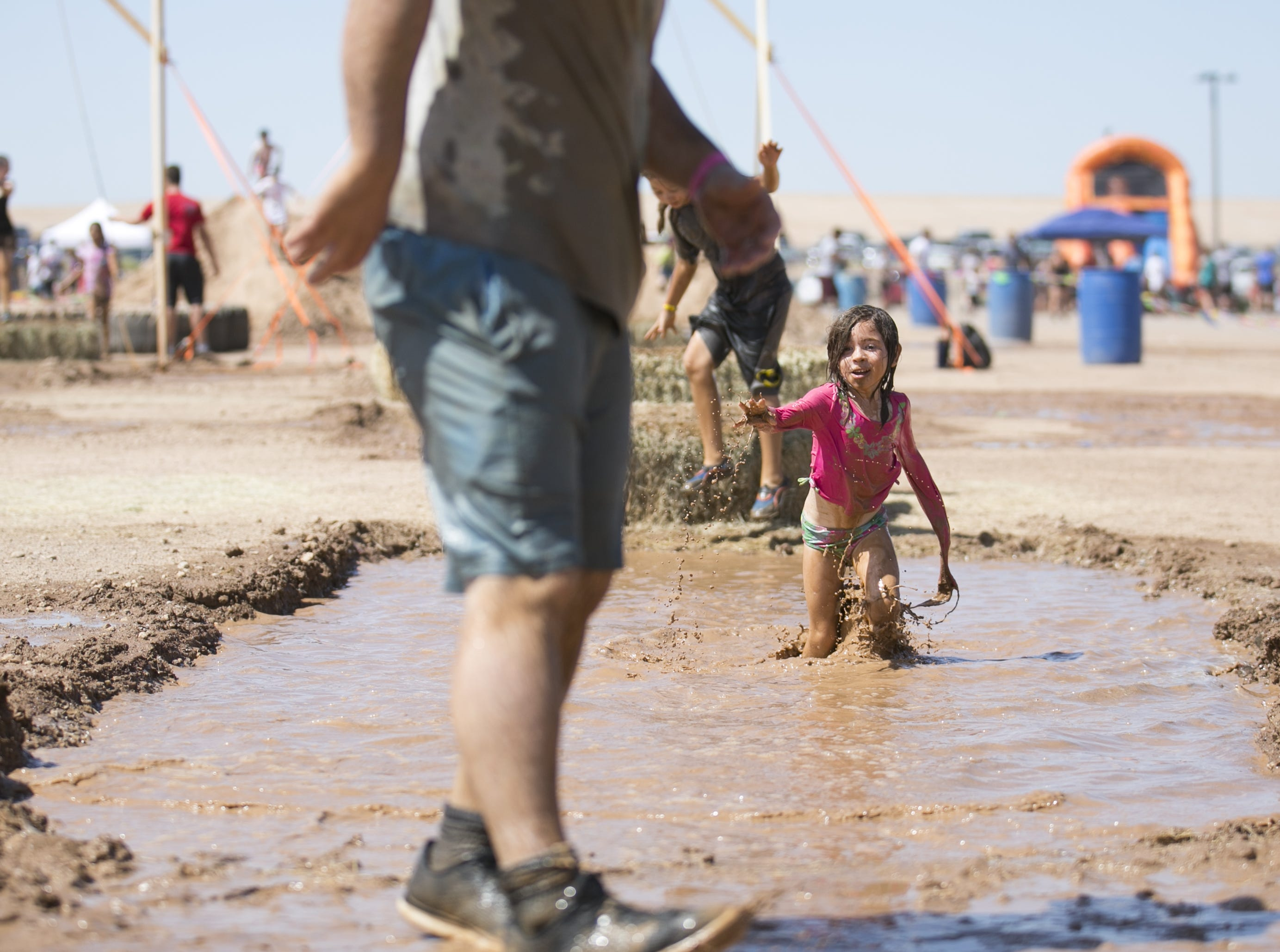 6-year-old Drusi Wallace (right) chases her dad Andrew Wallace (left) through the mud at the third annual Messy Fest in Queen Creek on Saturday, Sept. 15, 2018.