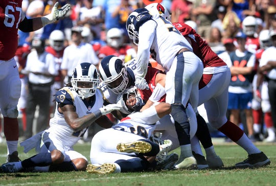 Cardinals quarterback Sam Bradford is sacked by the Rams defense during the first half of a game Sunday at Los Angeles Memorial Coliseum.