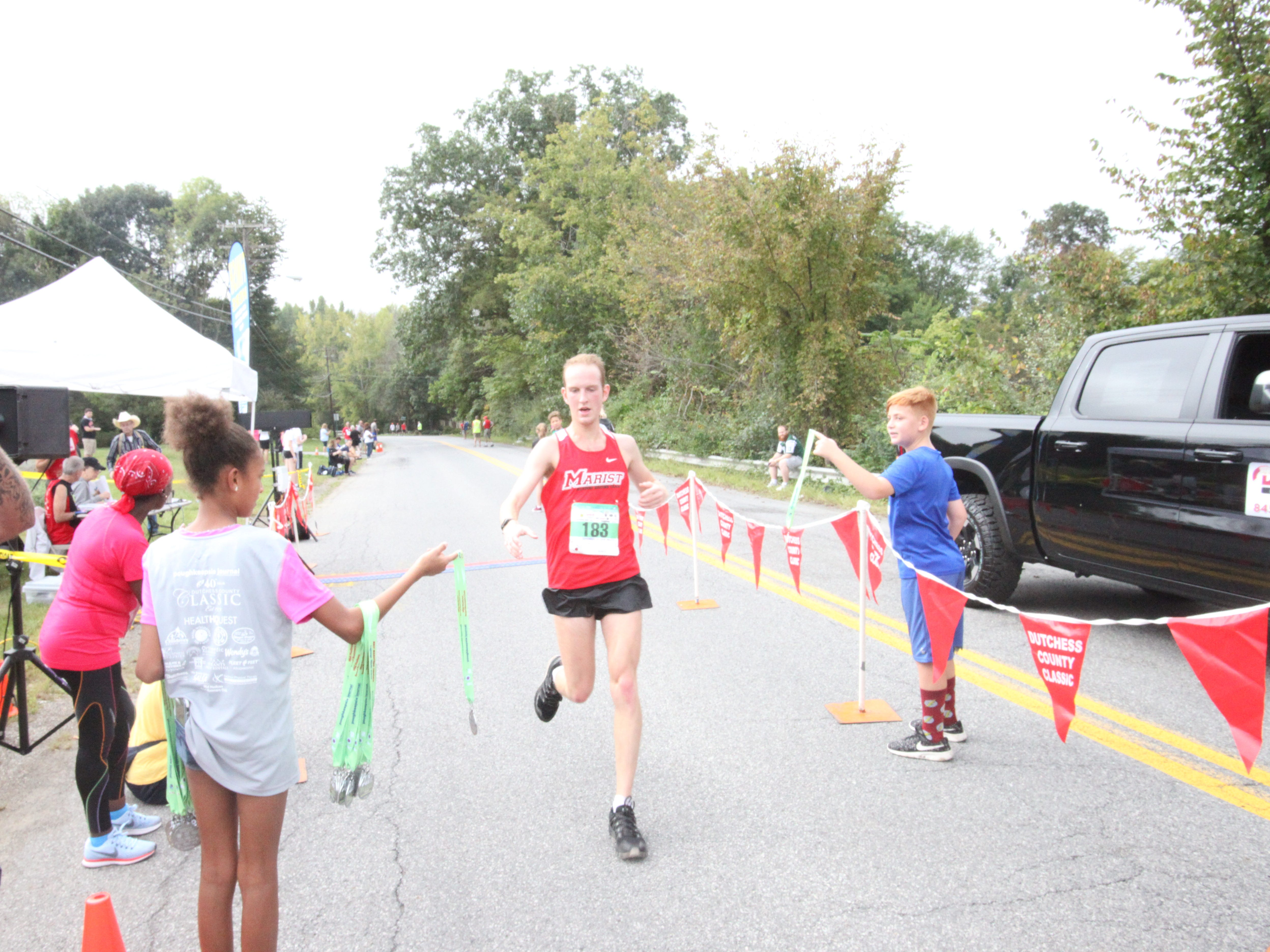 Dietrich Mosel, a former Marist College runner, crosses the finish line in second place in the men's half marathon at the Dutchess County Classic.