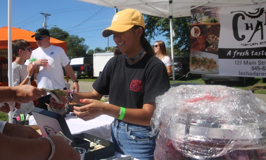 Sharai Martinez, a 16-year-old junior at New Paltz High School, collects money from a customer on Sunday during Taste of New Paltz. She works at her family's restaurant, La Charla Mexican Resturant in New Paltz.