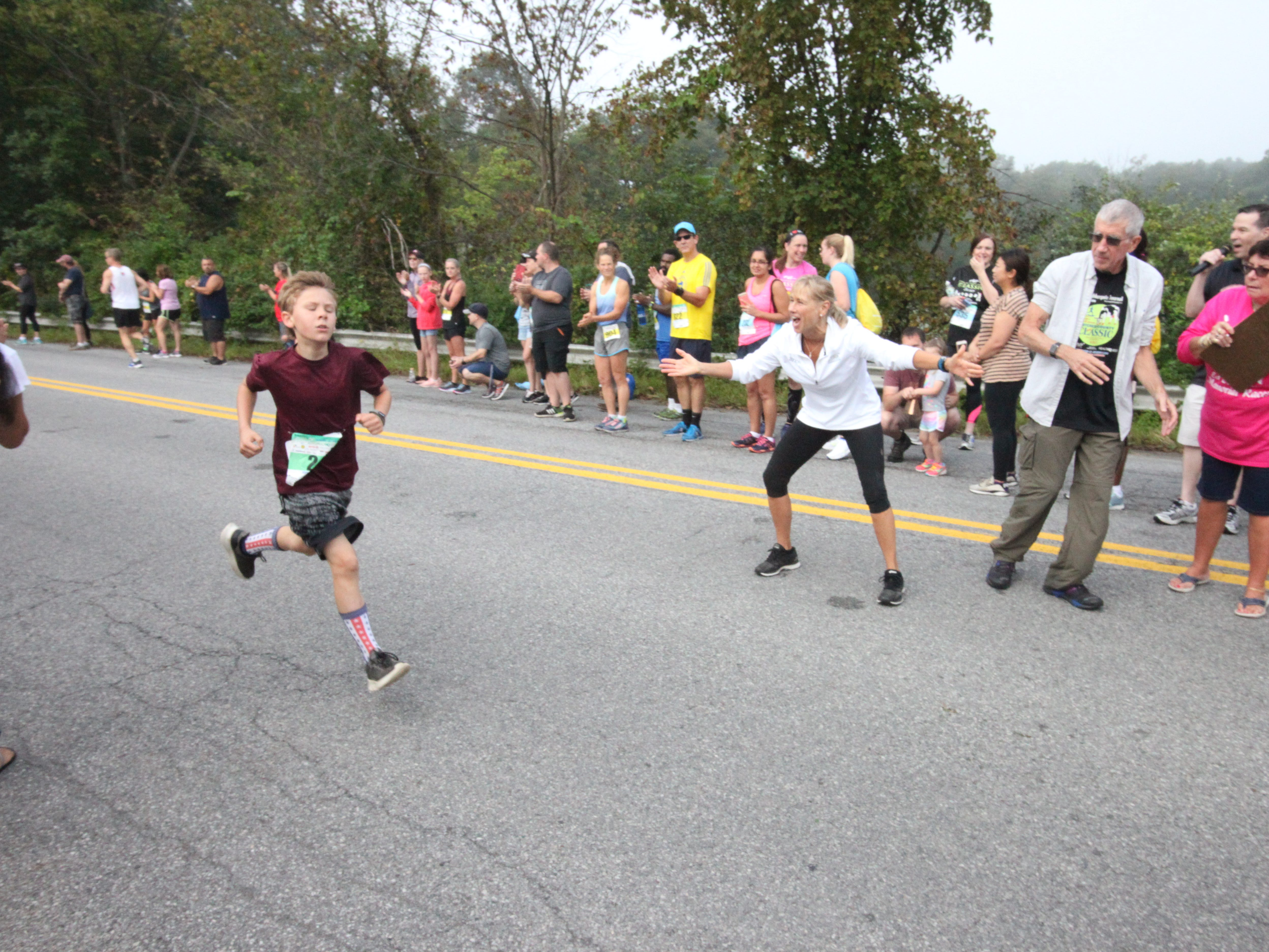 A young runner is implored to finish strong as he heads for the finish line of the 1-mile kids race at the Dutchess County Classic.