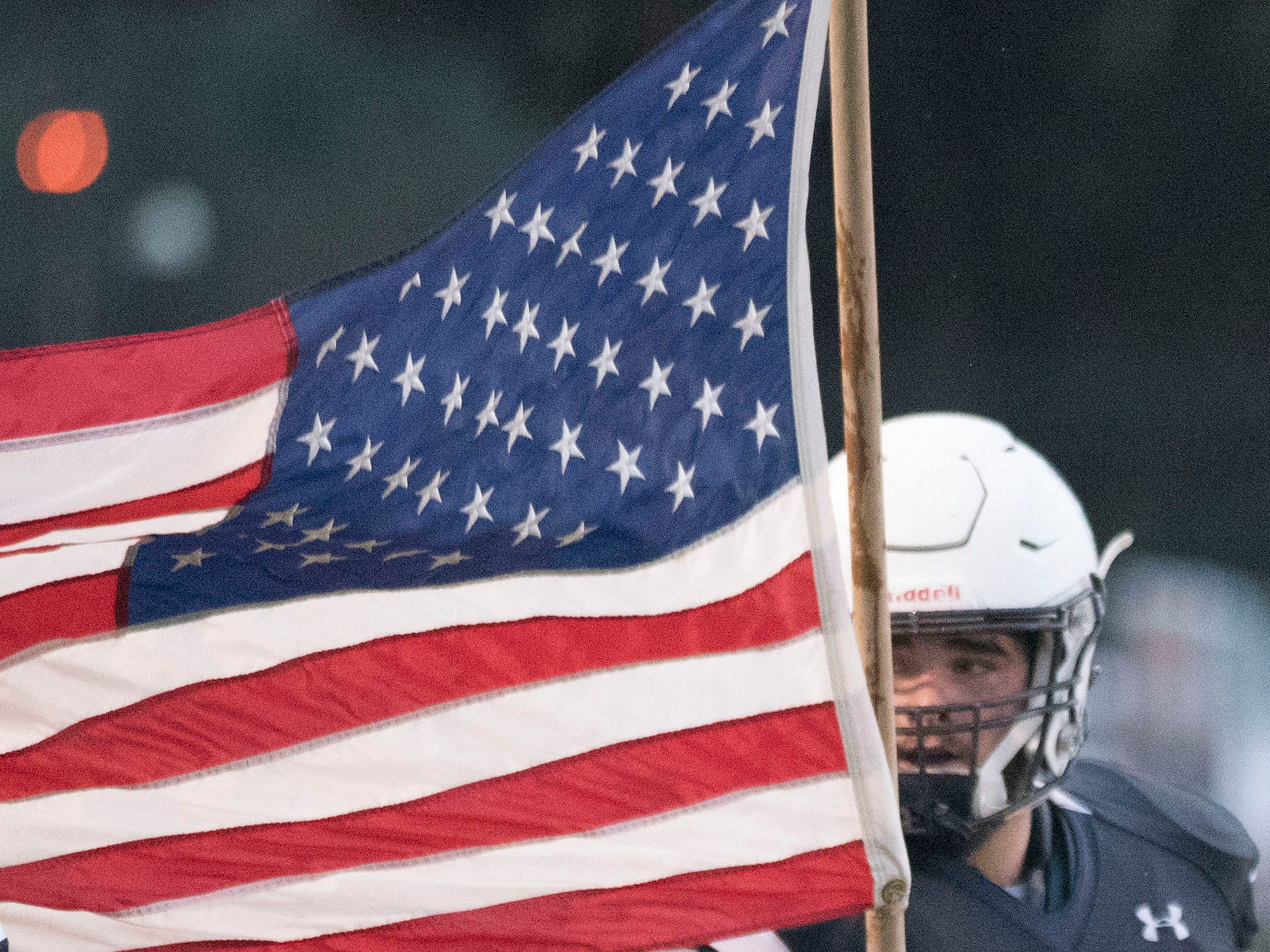 Chambersburg's Brock Harmon carries the American flag before the start of the Red Lion game. Chambersburg defeated Red Lion 28-19 in PIAA football on Friday, Sept. 7, 2018.