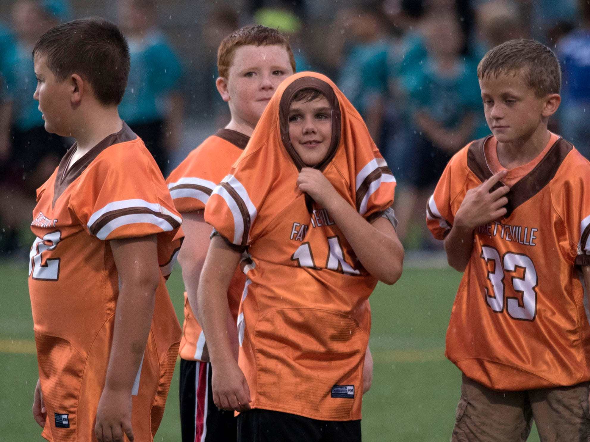 Chambersburg-area youth league football players weather the storm to watch the Trojans. Chambersburg defeated Red Lion 28-19 in PIAA football on Friday, Sept. 7, 2018.