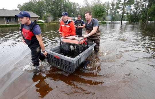 Members of the U.S. Coast Guard Shallow Water Rescue Team assist resident Joe Williams, right, in his flooded neighborhood in Lumberton, N.C., Sunday, Sept. 16, 2018, following flooding from Hurricane Florence . (AP Photo/Gerry Broome)