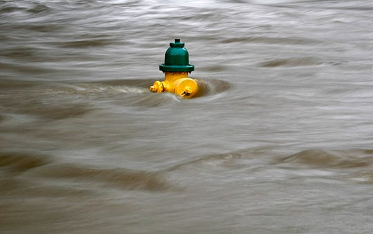 A fire hydrant is submerged in a flooded street as tropical depression Florence continues to dump heavy rain over the area in Fayetteville, N.C., Sunday, Sept. 16, 2018. (AP Photo/David Goldman)