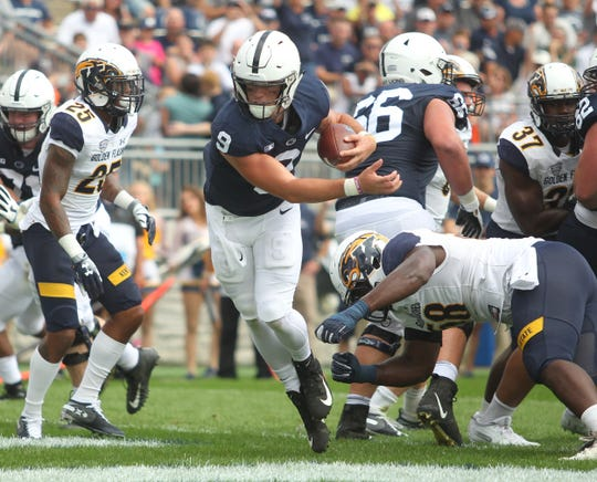 Quarterback Trace McSorley avoids a tackle attempt by Theo Eboigbe to score a touchdown in a 63-10 win over Kent State on Saturday, Sept. 15, 2018, at Beaver Stadium in University Park, Pennsylvania.