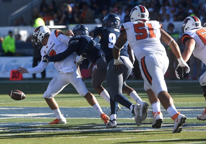 Nevada's Asauni Rufus (2) forces a fumble while sacking Oregon State quarterback Conor Blount (2) during Saturday's game at Mackay Stadium.