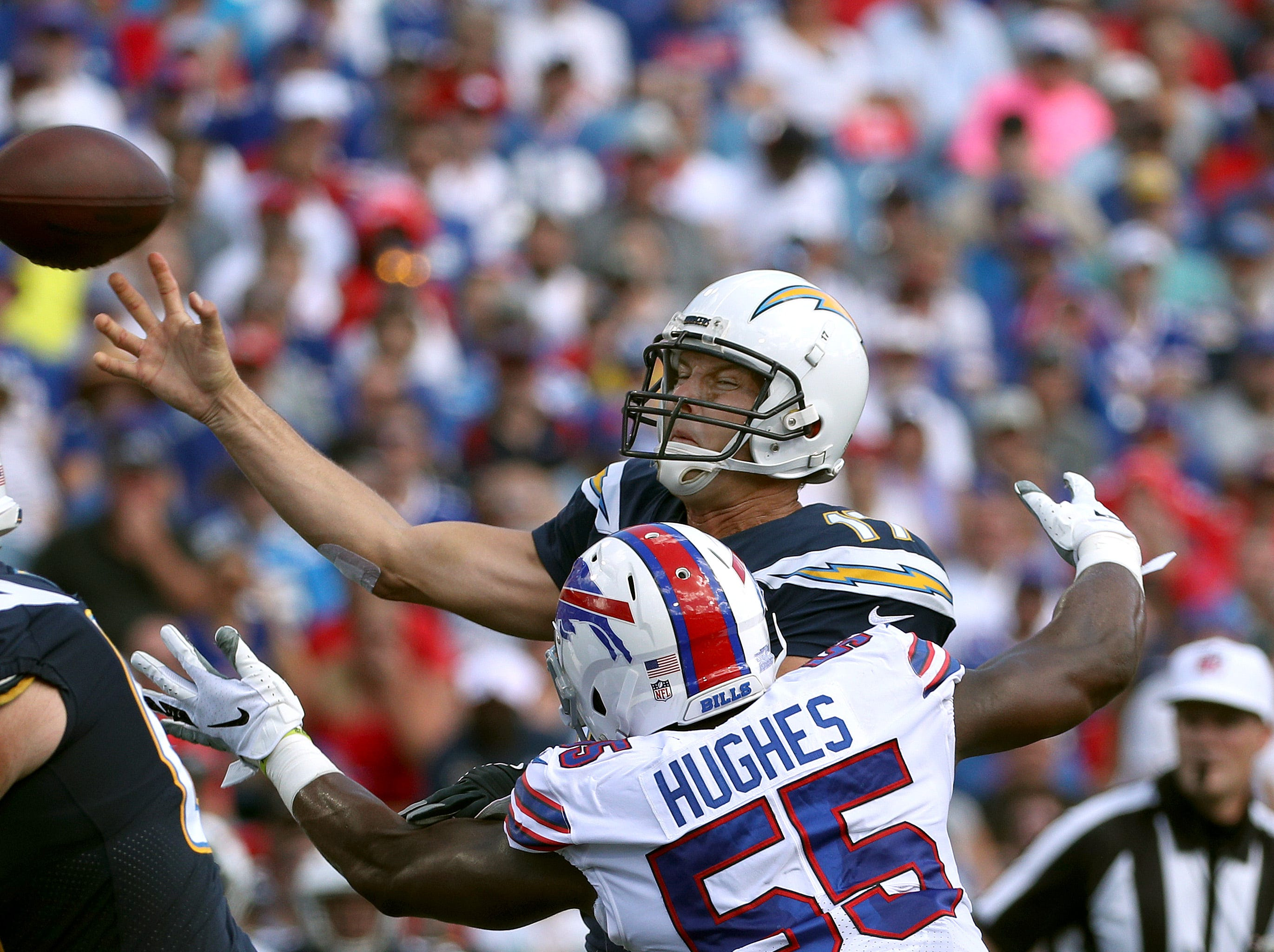 Chargers quarterback Philip Rivers delivers the ball as he is hit by Bills Jerry Hughes.