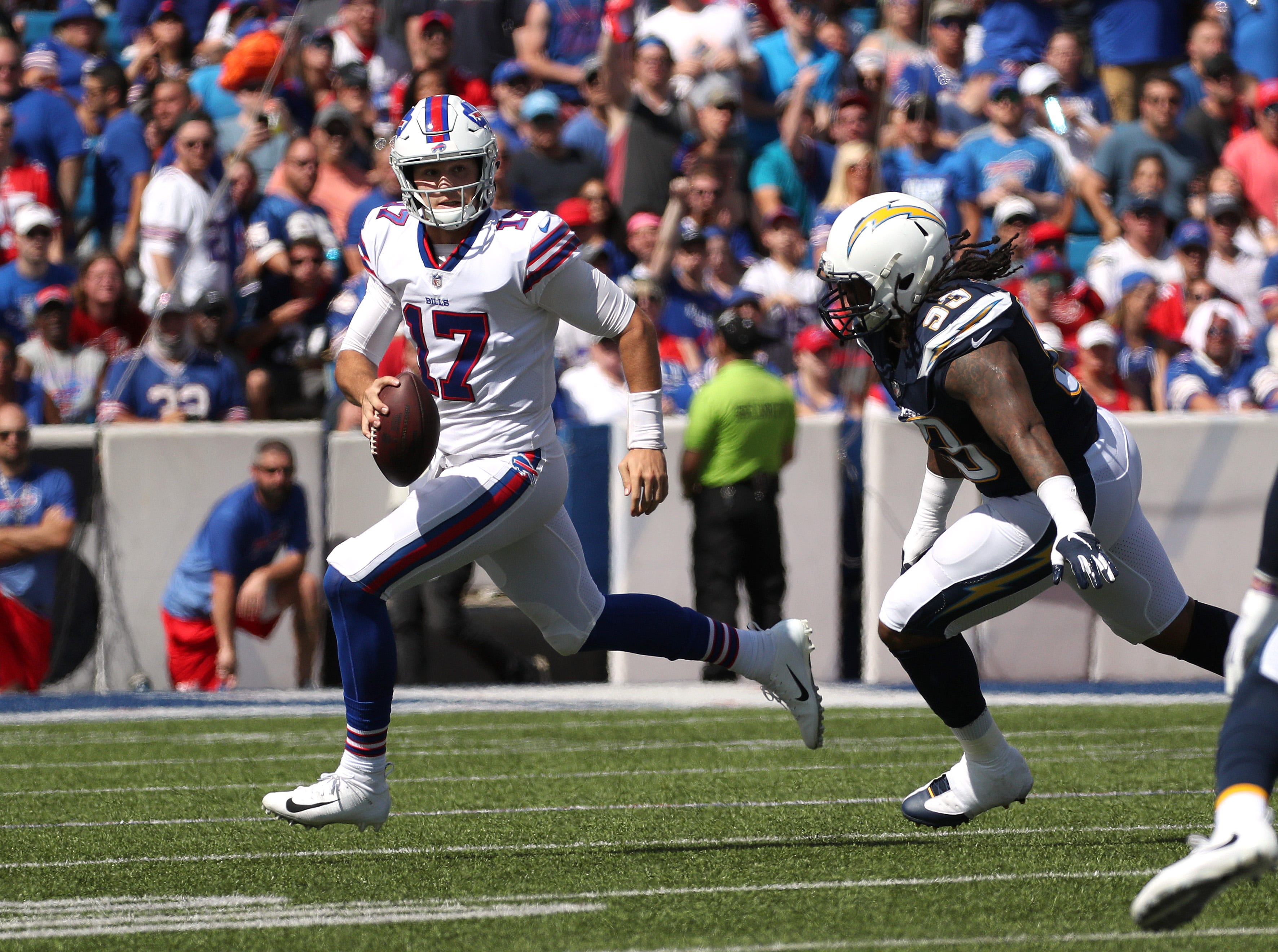 Bills quarterback Josh Allen is chased out of the pocket by Chargers Darius Philon.