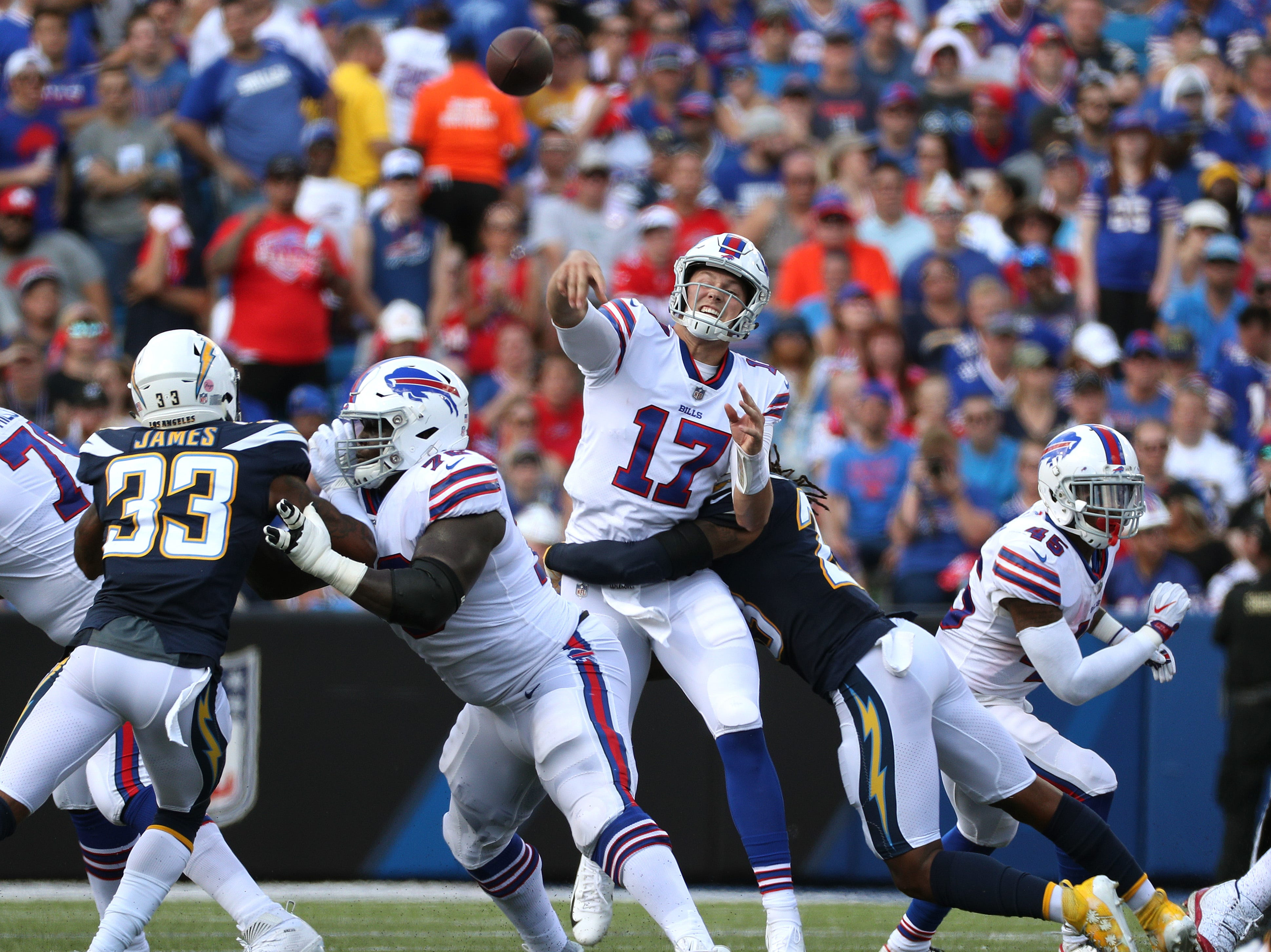 Bills quarterback Josh Allen delivers a pass as he is hit.