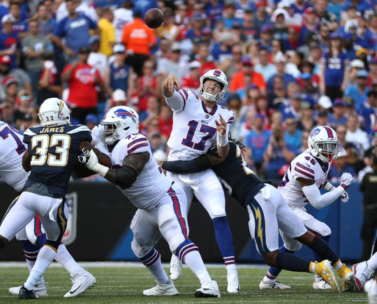 Bills quarterback Josh Allen delivers a pass as he is hit.