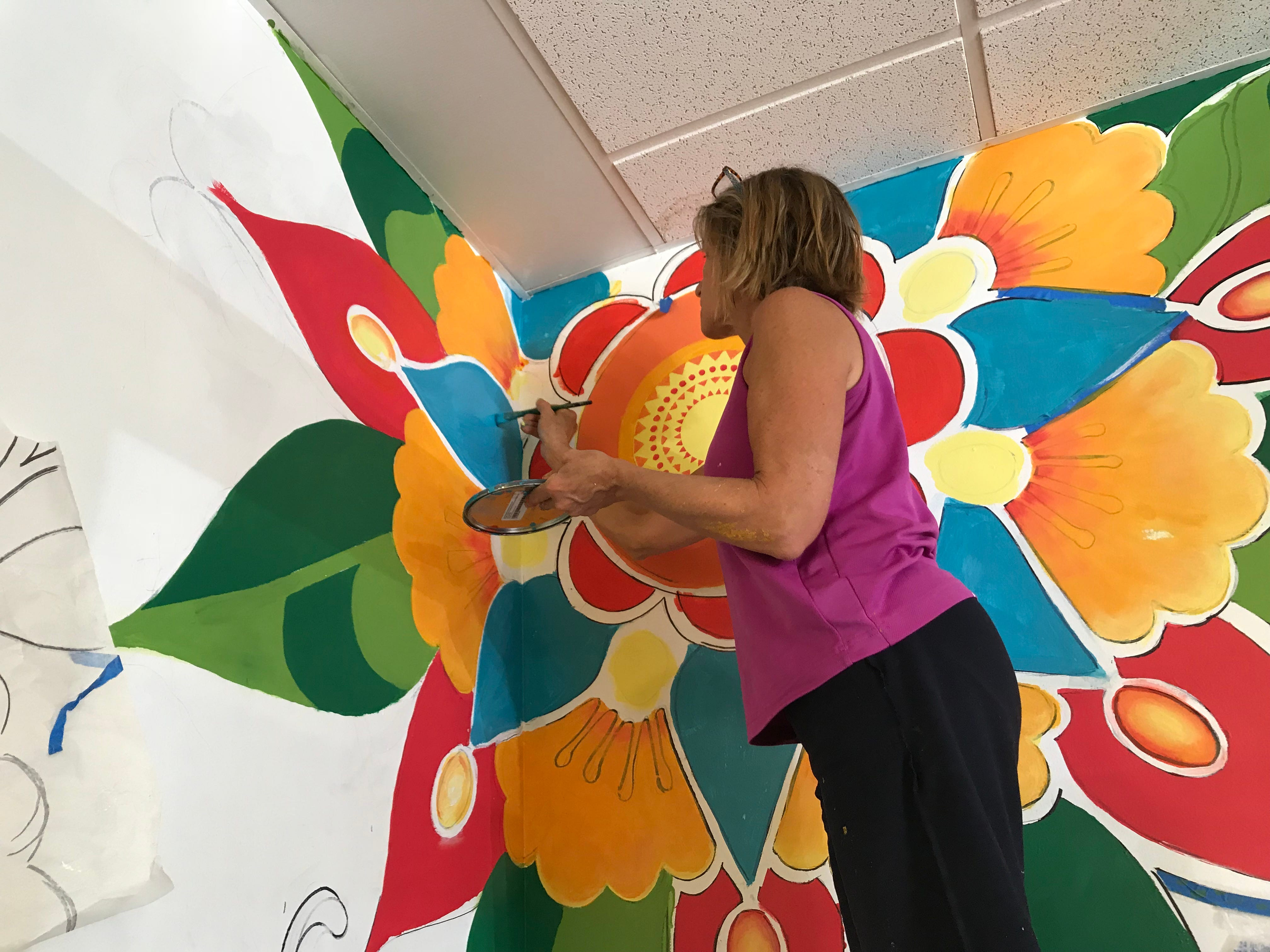 Colleen L'Hommedieu paints a mural at the Itacate in Chili.