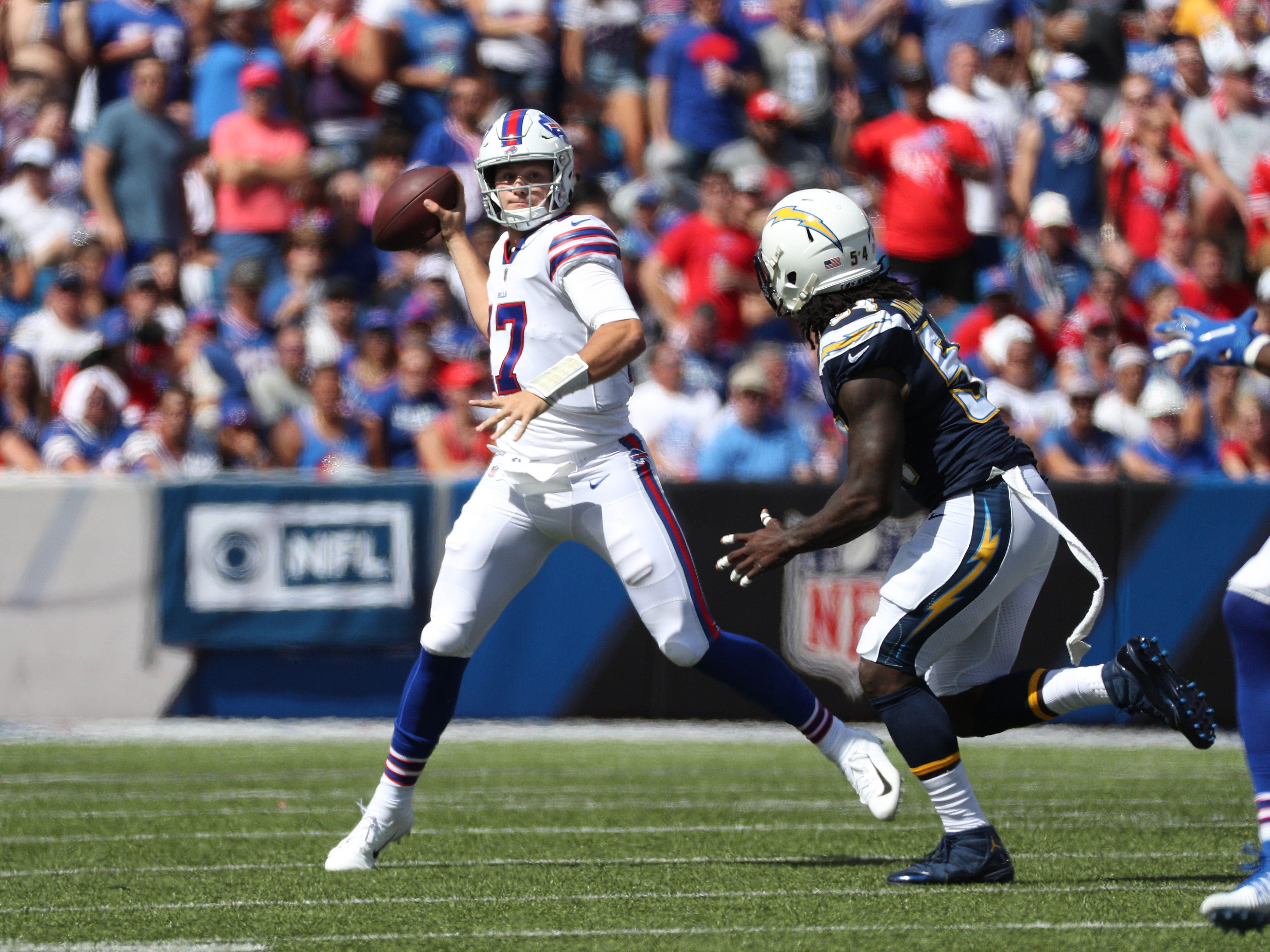 Bills quarterback Josh Allen rolls out of the pocket to throw a pass.