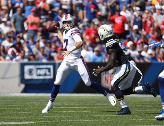 Bills quarterback Josh Allen rolls out of the pocket to throw a pass.
