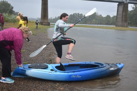 A family member of a participant helps her get into the kayak to begin the second leg of the race on the Willamette Valley River.